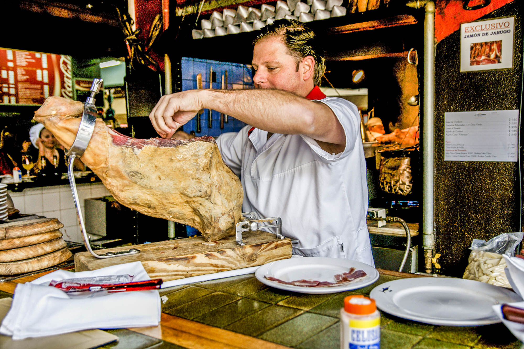 Waiter cuts slices of ham at a restaurant in Montevideo