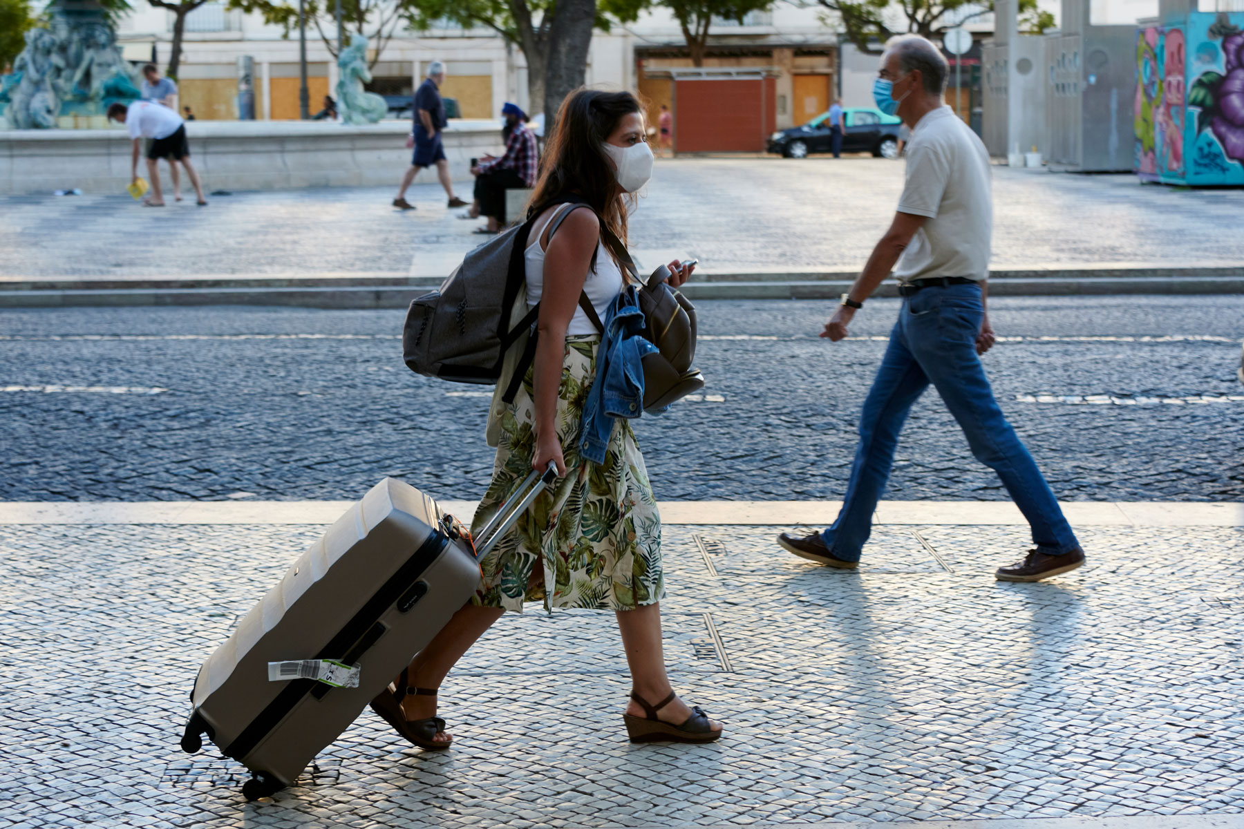 woman walking down the street pulling a suitcase