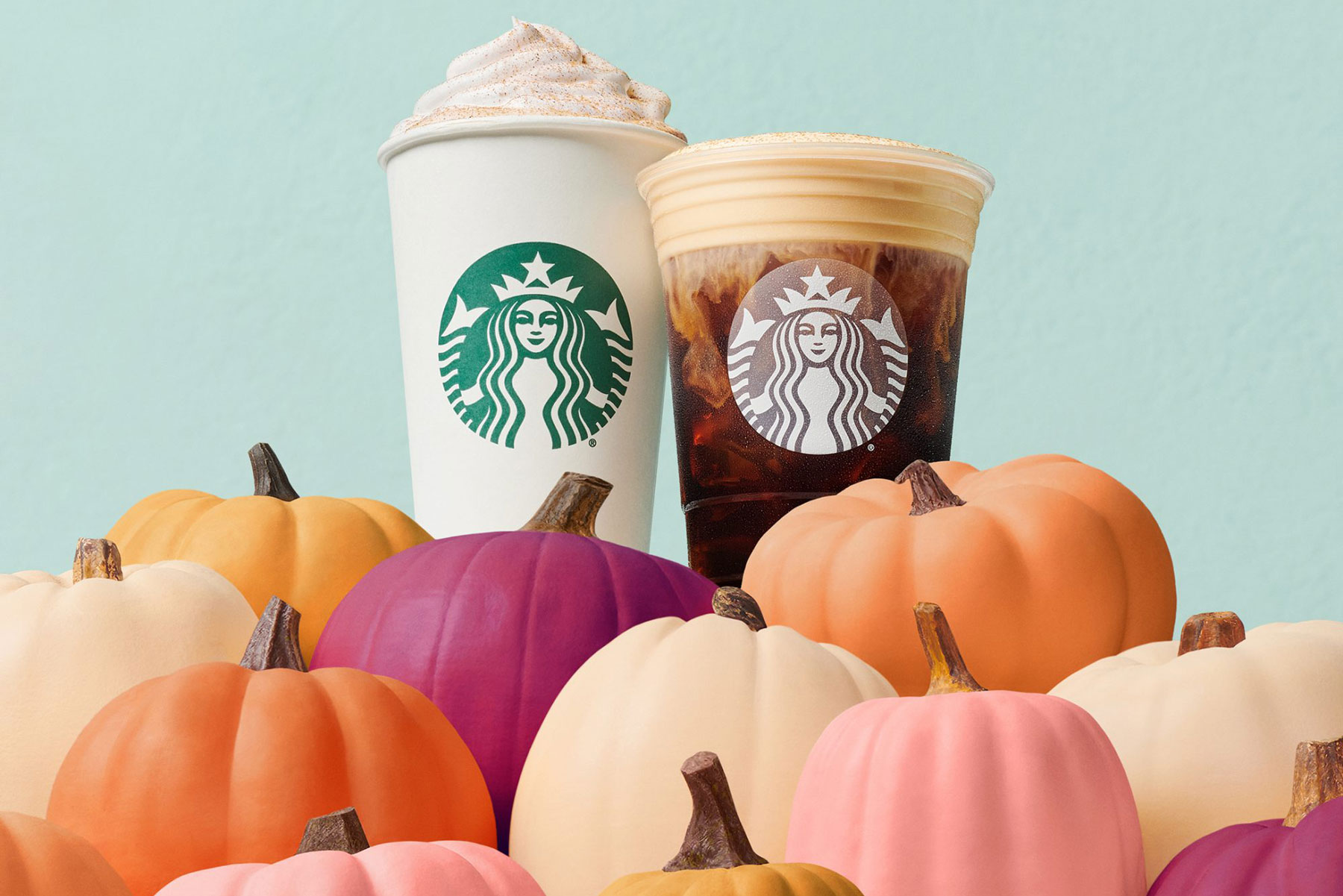 Starbucks latte and cold brew atop a pile of pumpkins