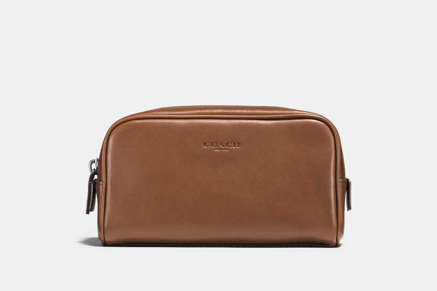 A brown leather Dopp kit made by Coach