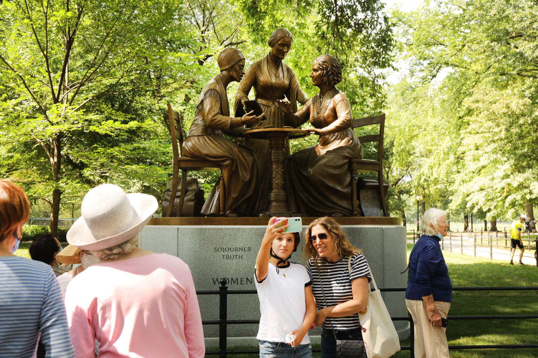 visitors photographing statue of women's rights pioneers Sojourner Truth, Susan B Anthony, and Elizabeth Cady Stanton in Central Park