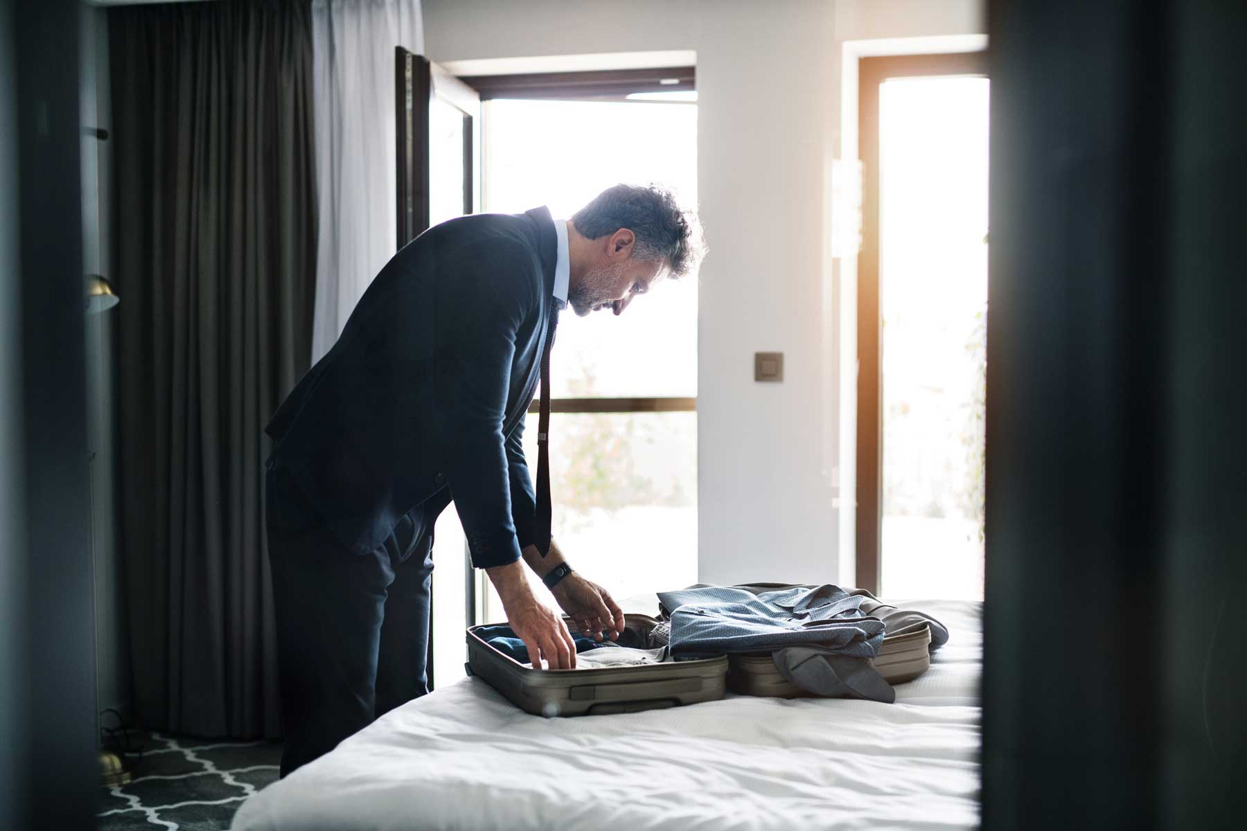Mature businessman unpacking in a hotel room.