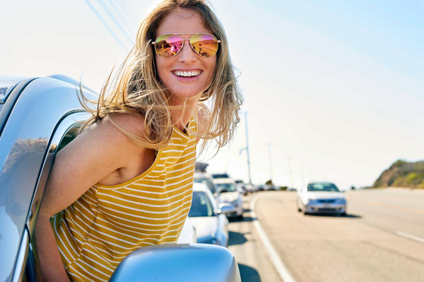 Happy young woman leaning out of car window wearing sunglasses