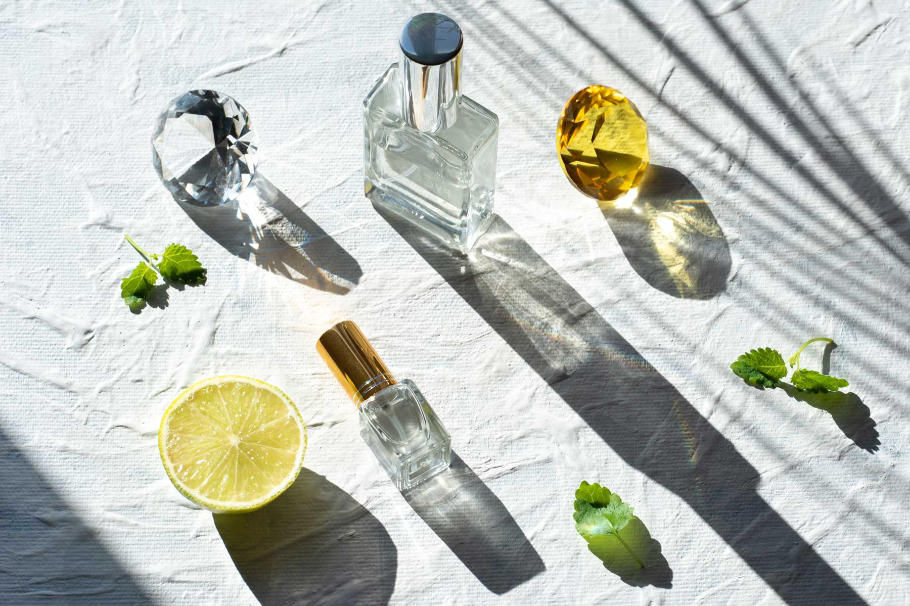 Transparent perfume bottle on a white background. Bright sunlight.