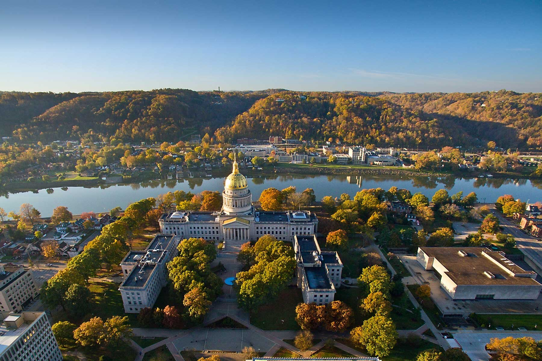 Aerial view of Charleston, West Virginia on a sunny autumn day, showing the river and capitol building