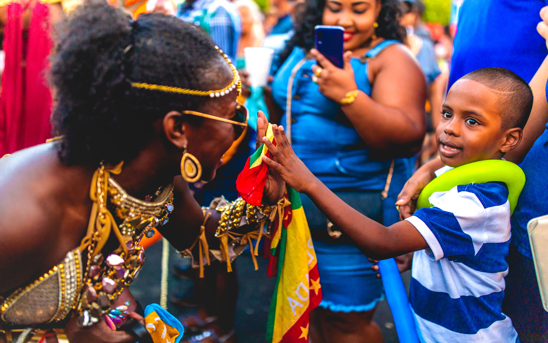 Woman giving high five to boy during Carnival