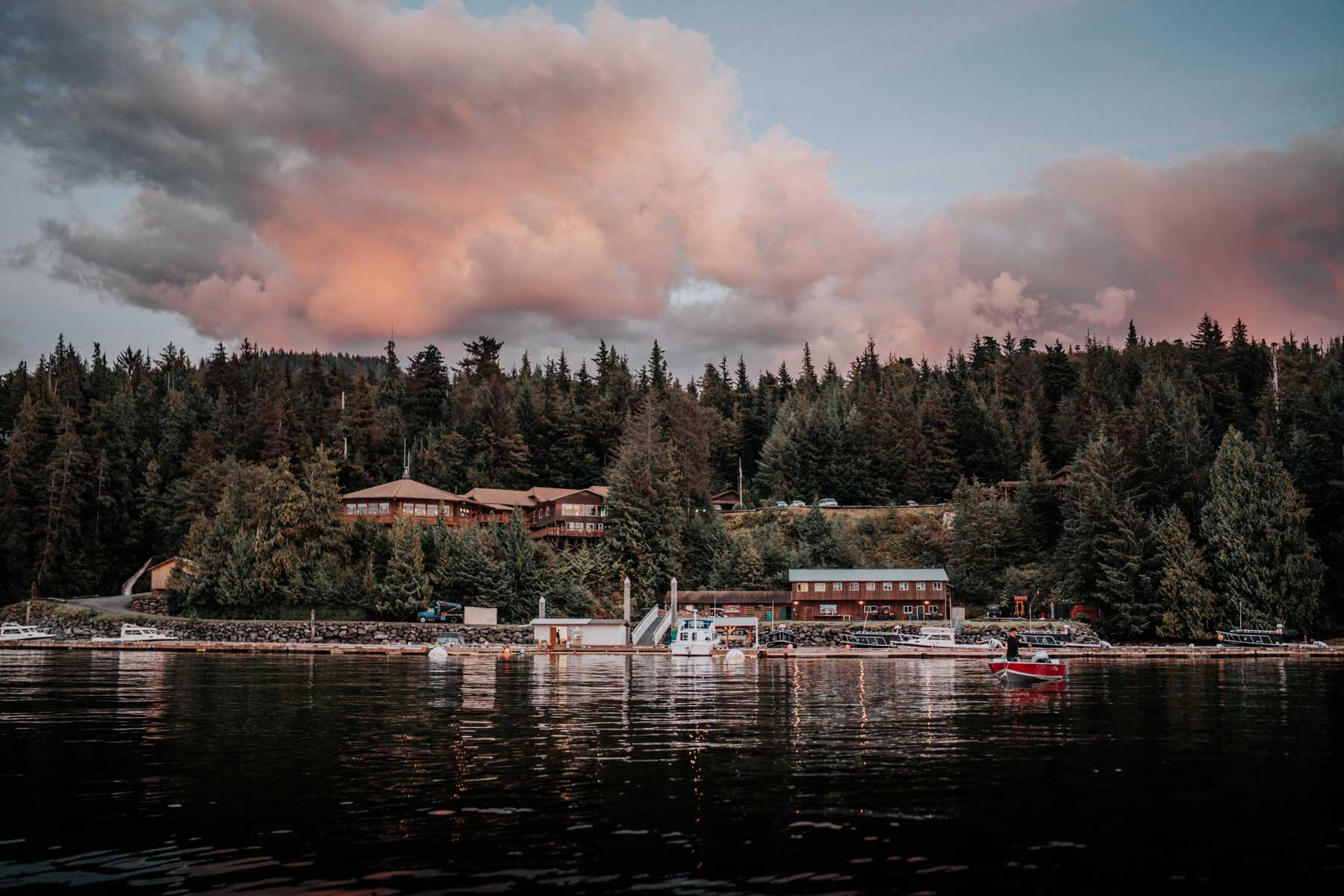 Exterior view of Salmon Falls resort in Alaska from the water, surrounded by tall pine trees