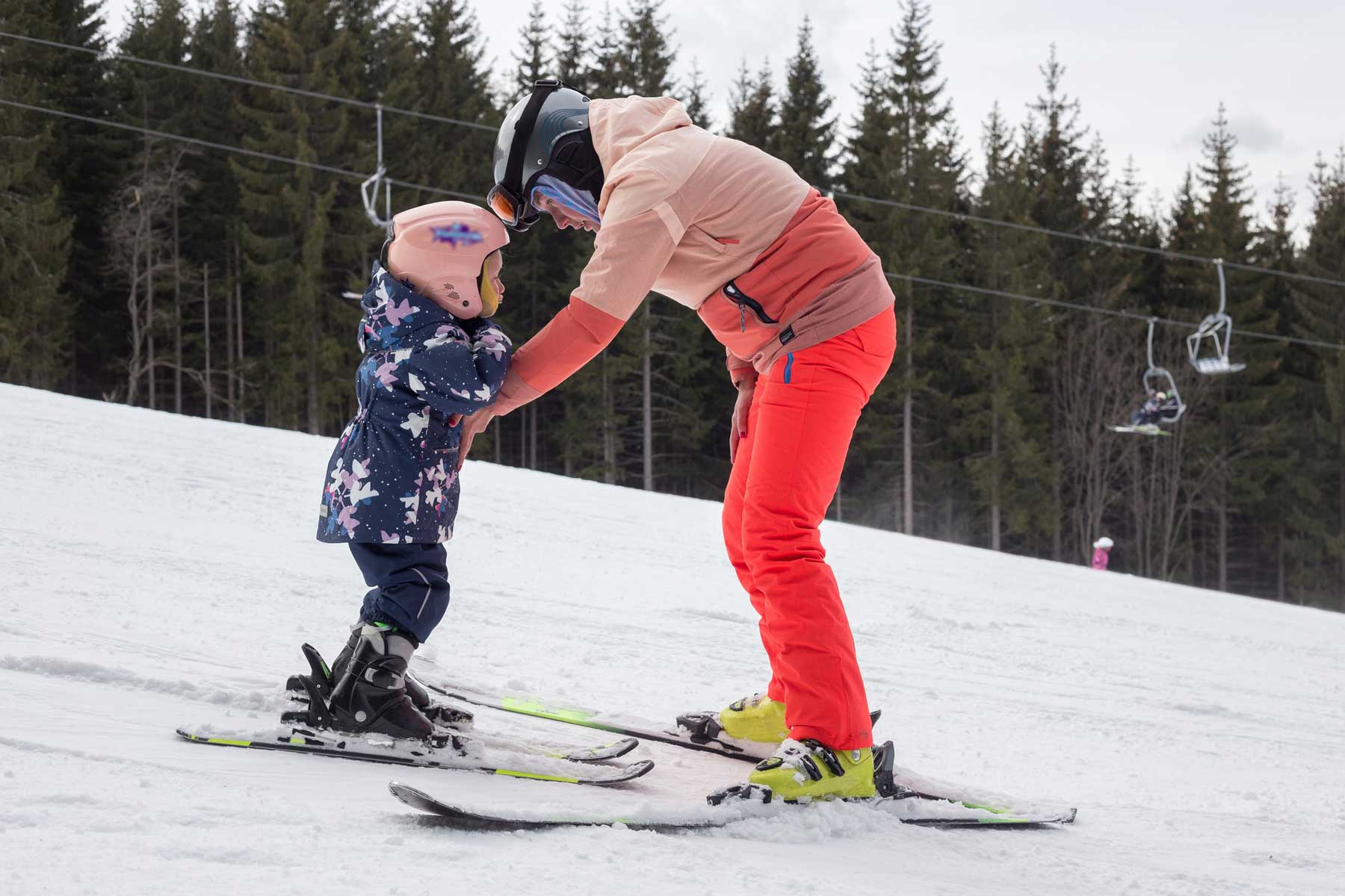 Young woman teaches child to ski