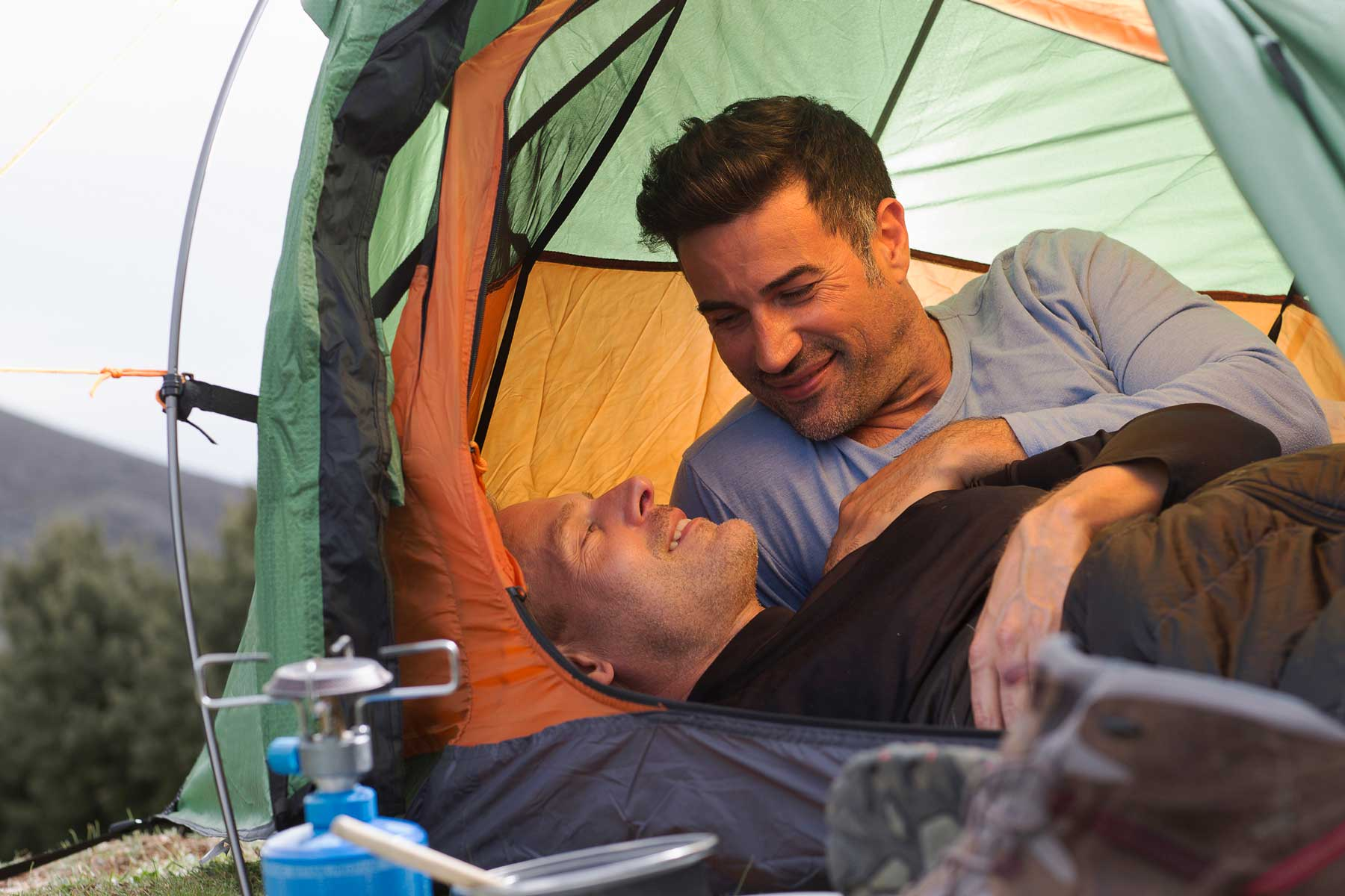 Male couple resting in a camping tent