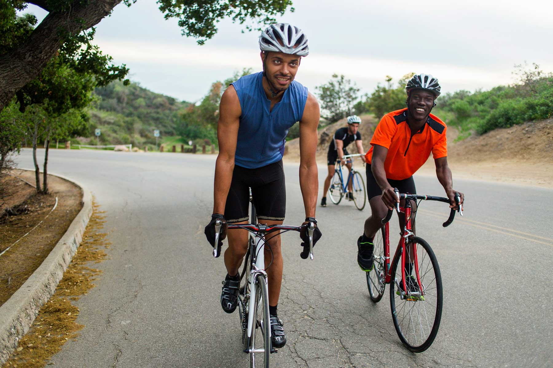 Three cyclists on uphill road in California