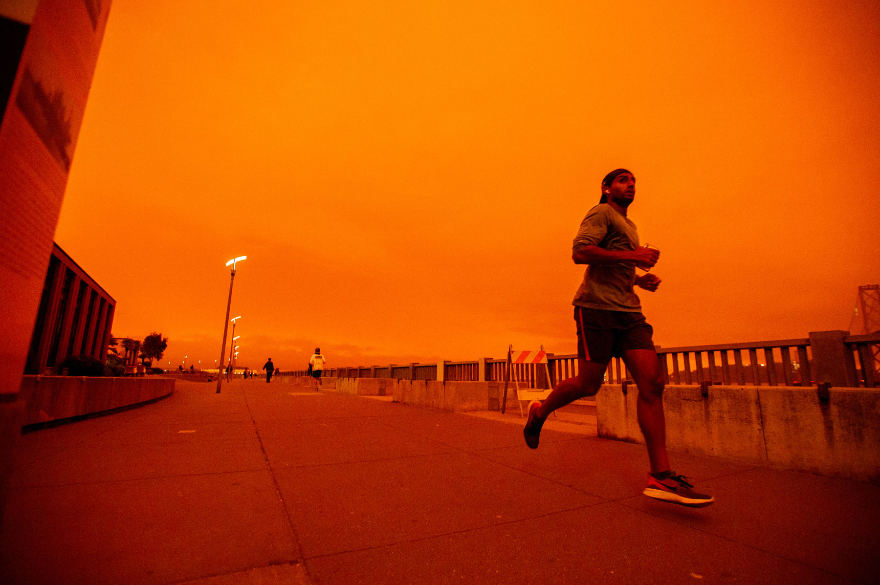 man jogging with red-orange sky in the background