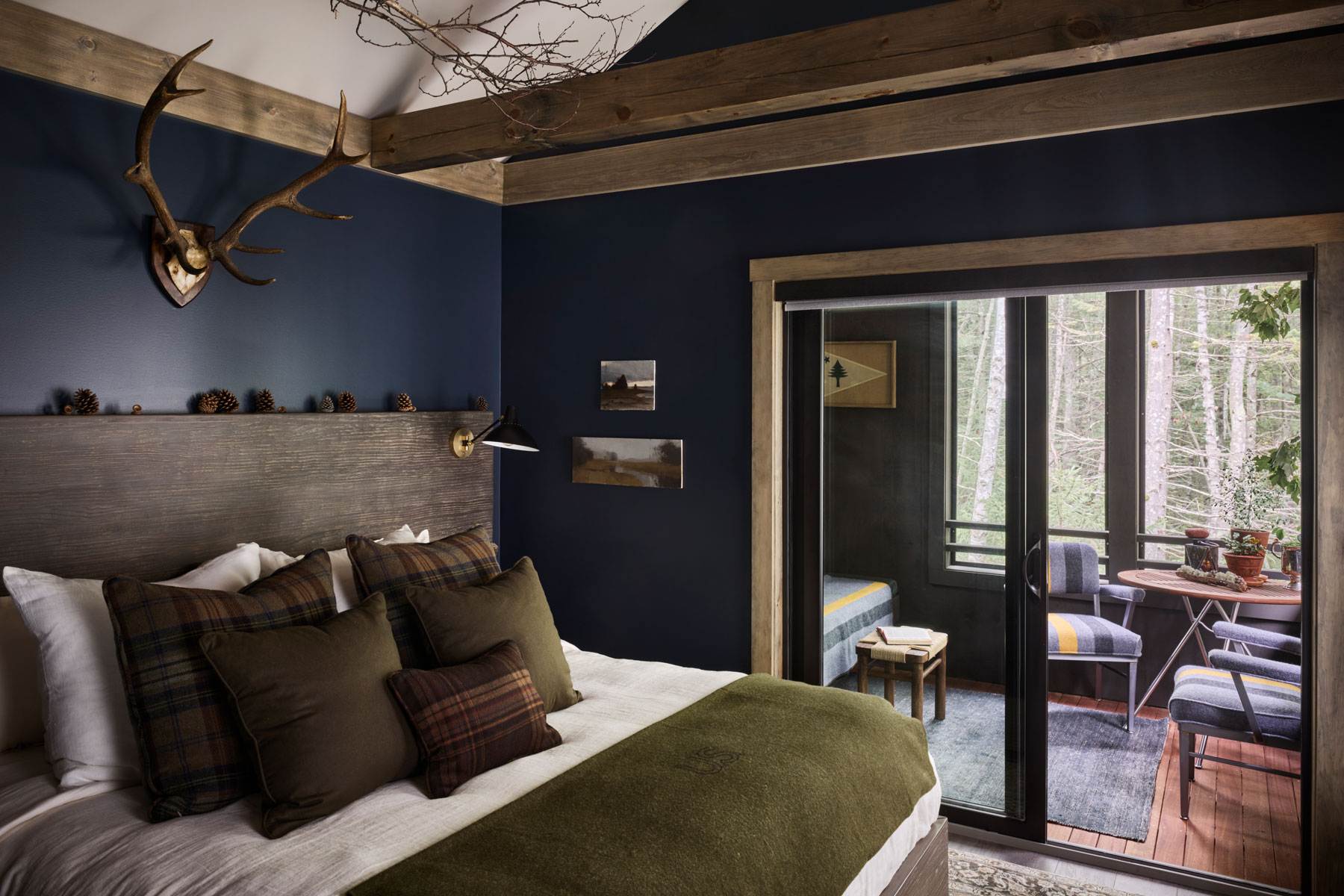 Dark blue room with wooden bed and antlers on wall by sliding glass door to living room