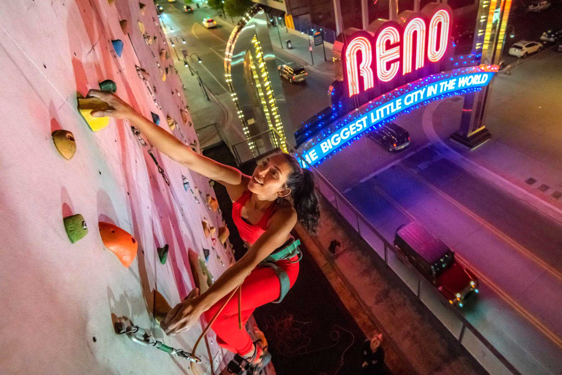 Woman climbing wall of Whitney Peak Hotel at night in Reno, NV