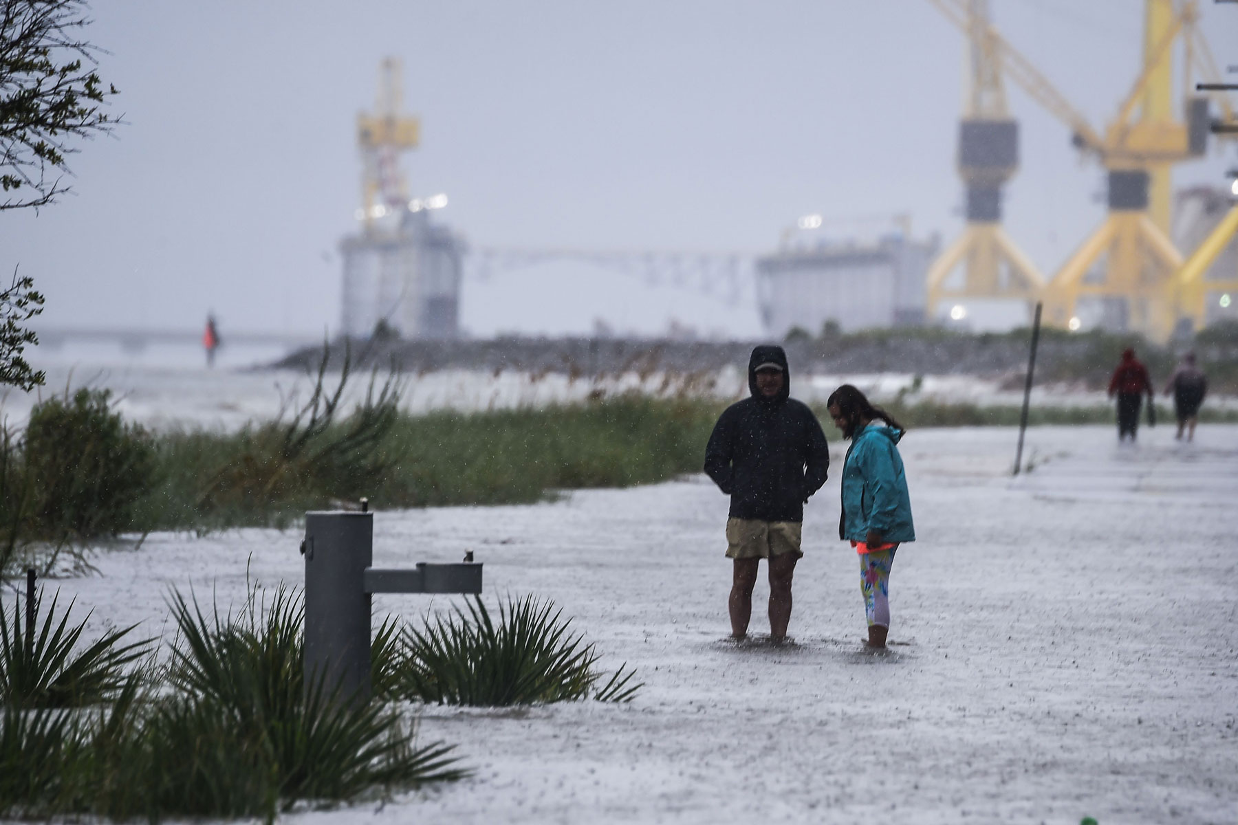 Residents walk on the costal road before Hurricane Sally makes landfall