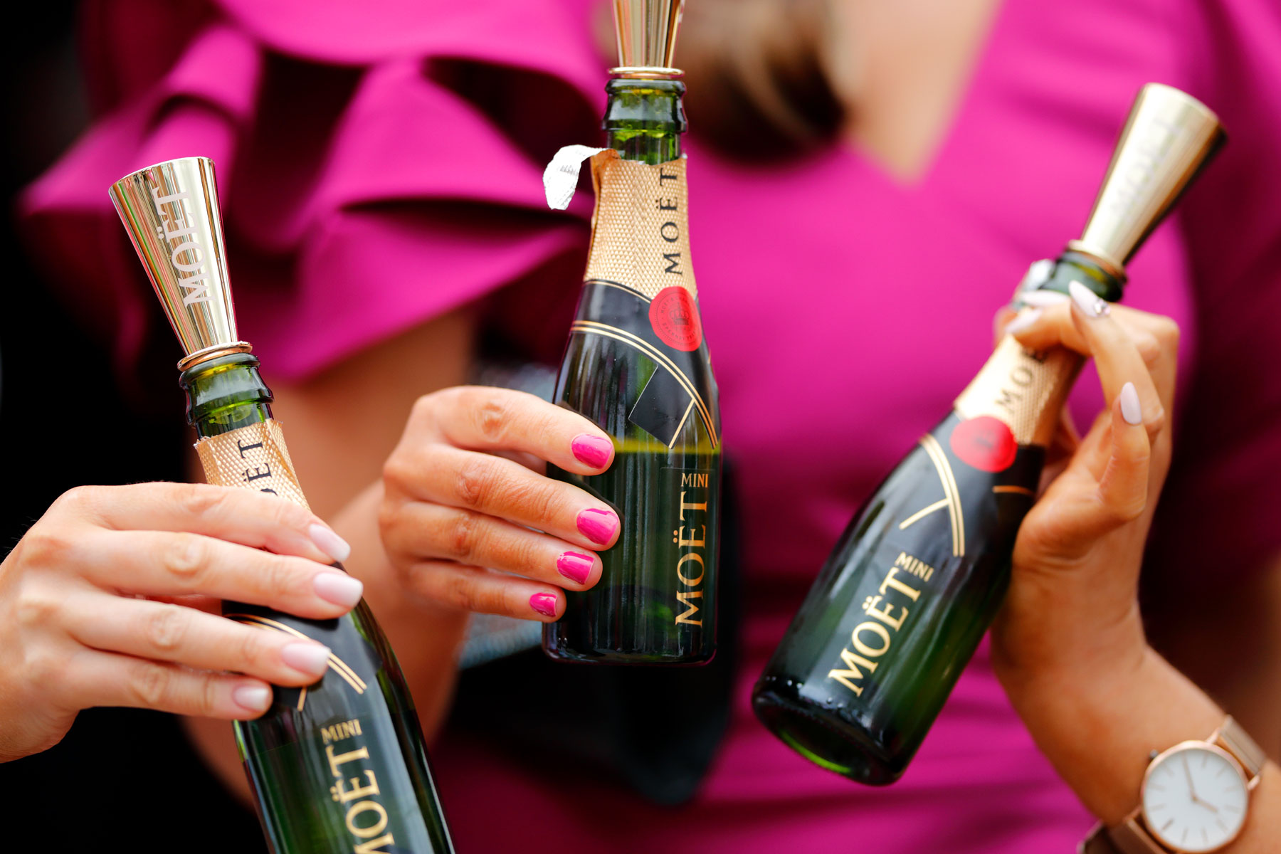 hands holding mini bottles of Moet Champagne