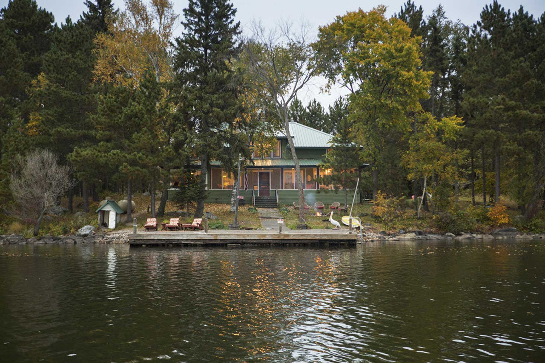 A private island cabin tucked away off a body of water with a deck
