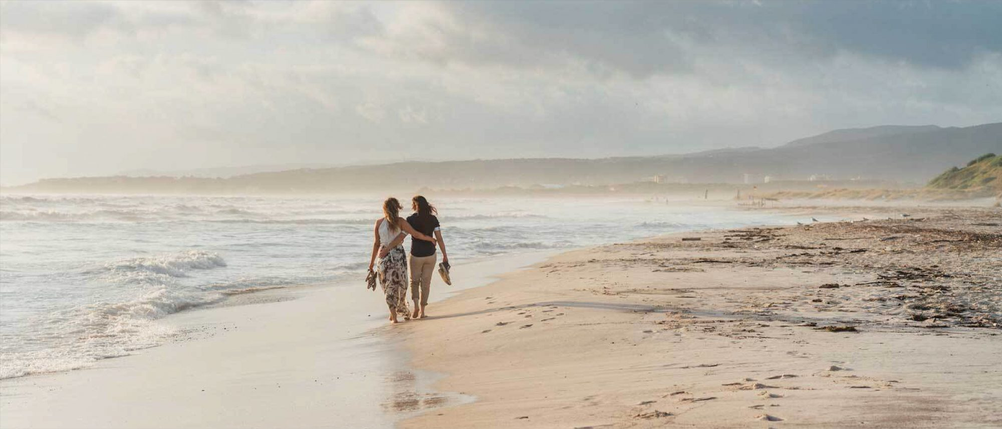 Two women walking on a beach during the day.