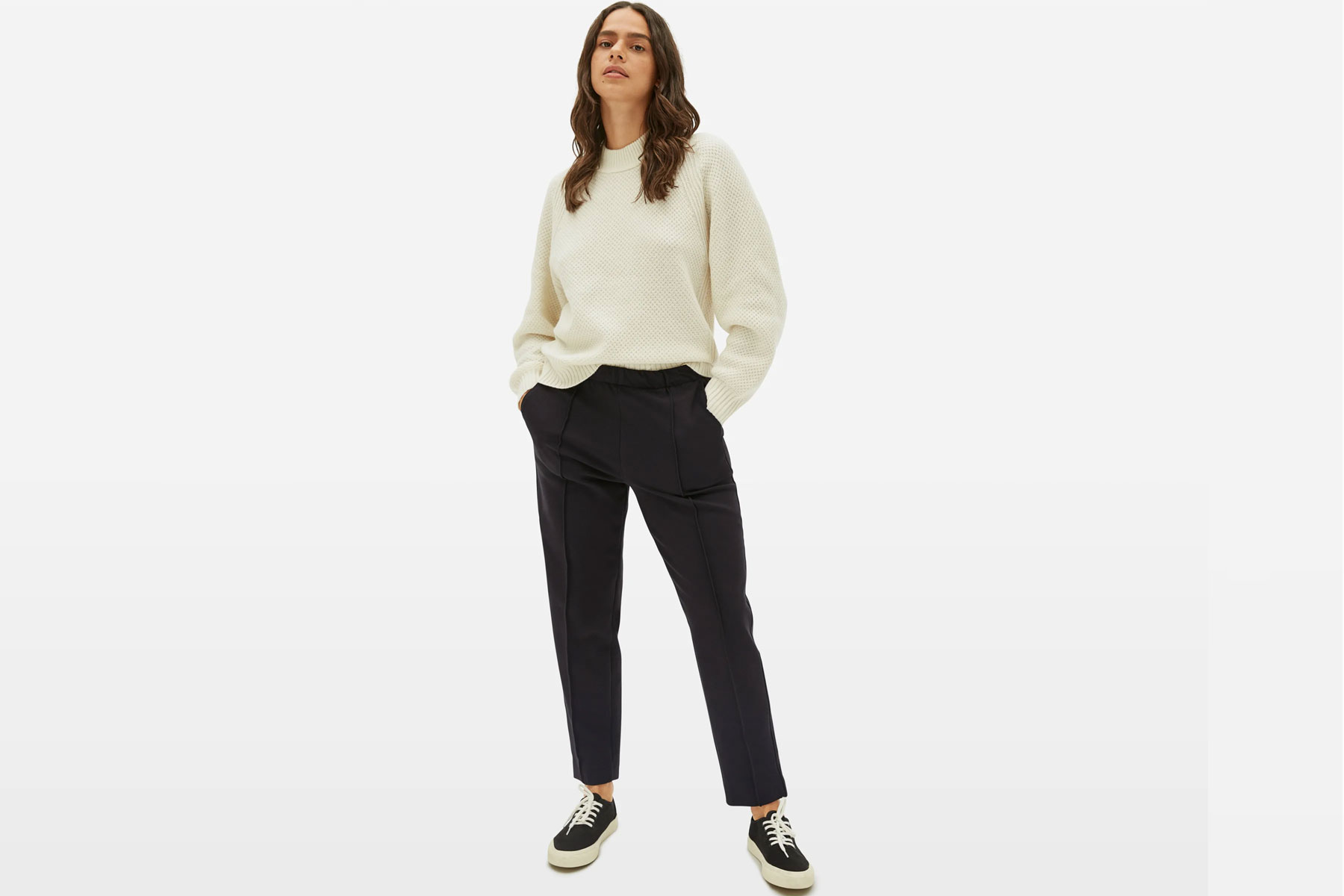 Woman wearing white sweater and black pants
