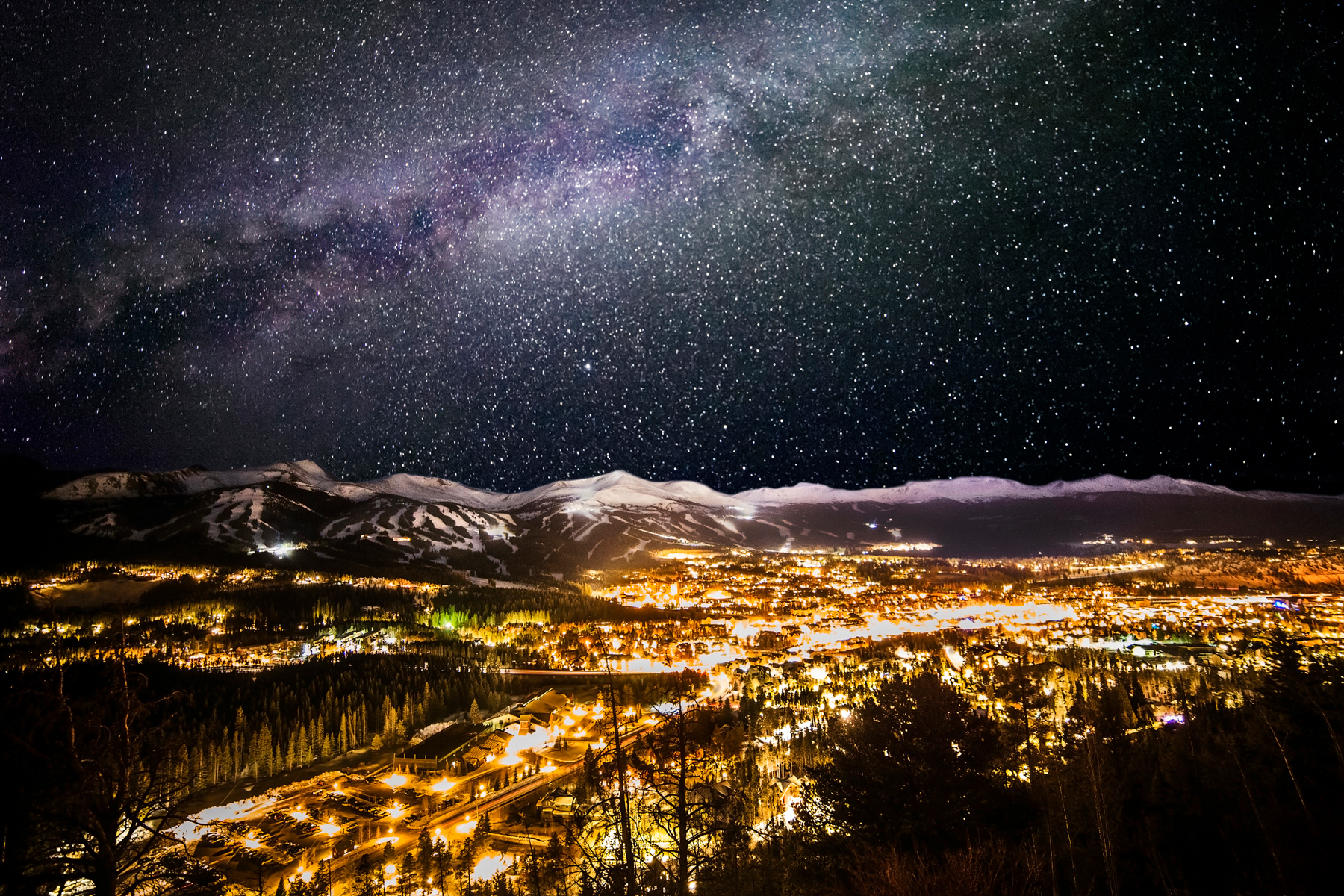 Winter time in Breckenridge, CO as it glows at night with the Milky Way above.