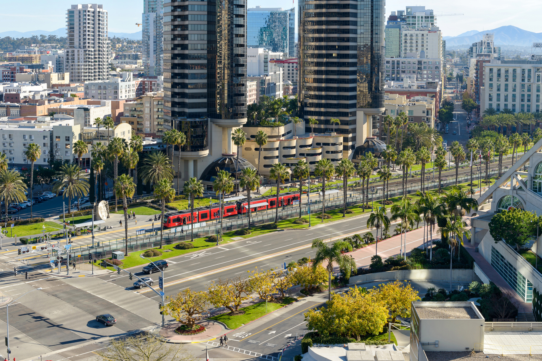 An aerial view of a red San Diego Trolley stopping at a station on East Harbor Drive in Marina District of Downtown San Diego, California