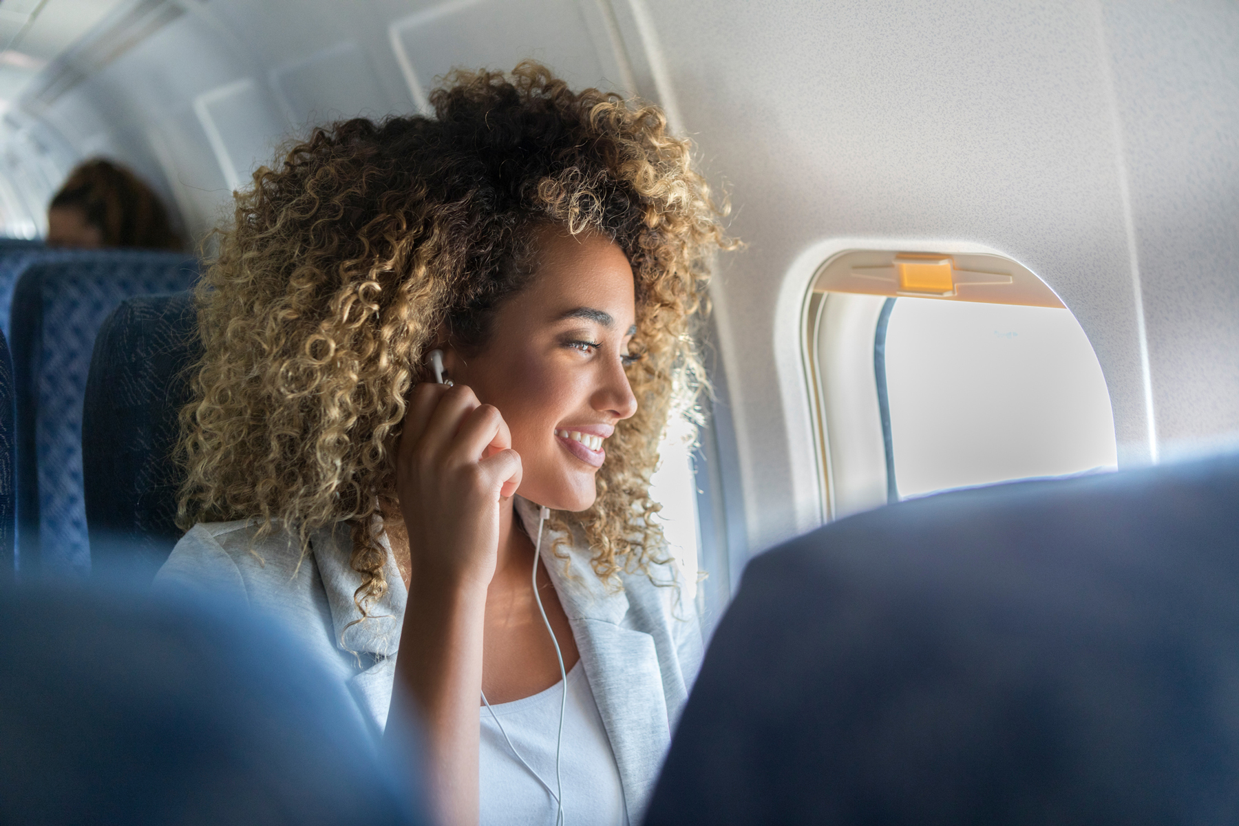 A young woman look out a plane window smiles