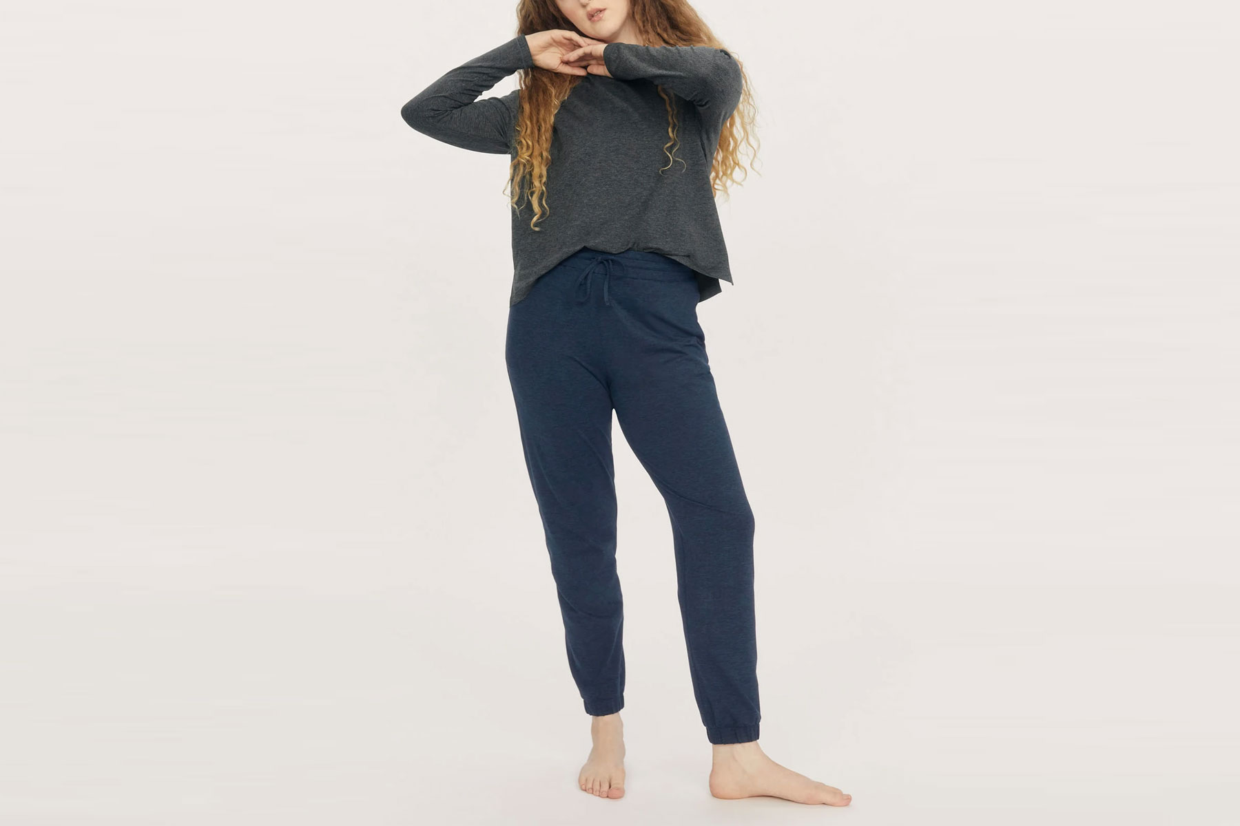 Woman wearing navy joggers and grey sweatshirt