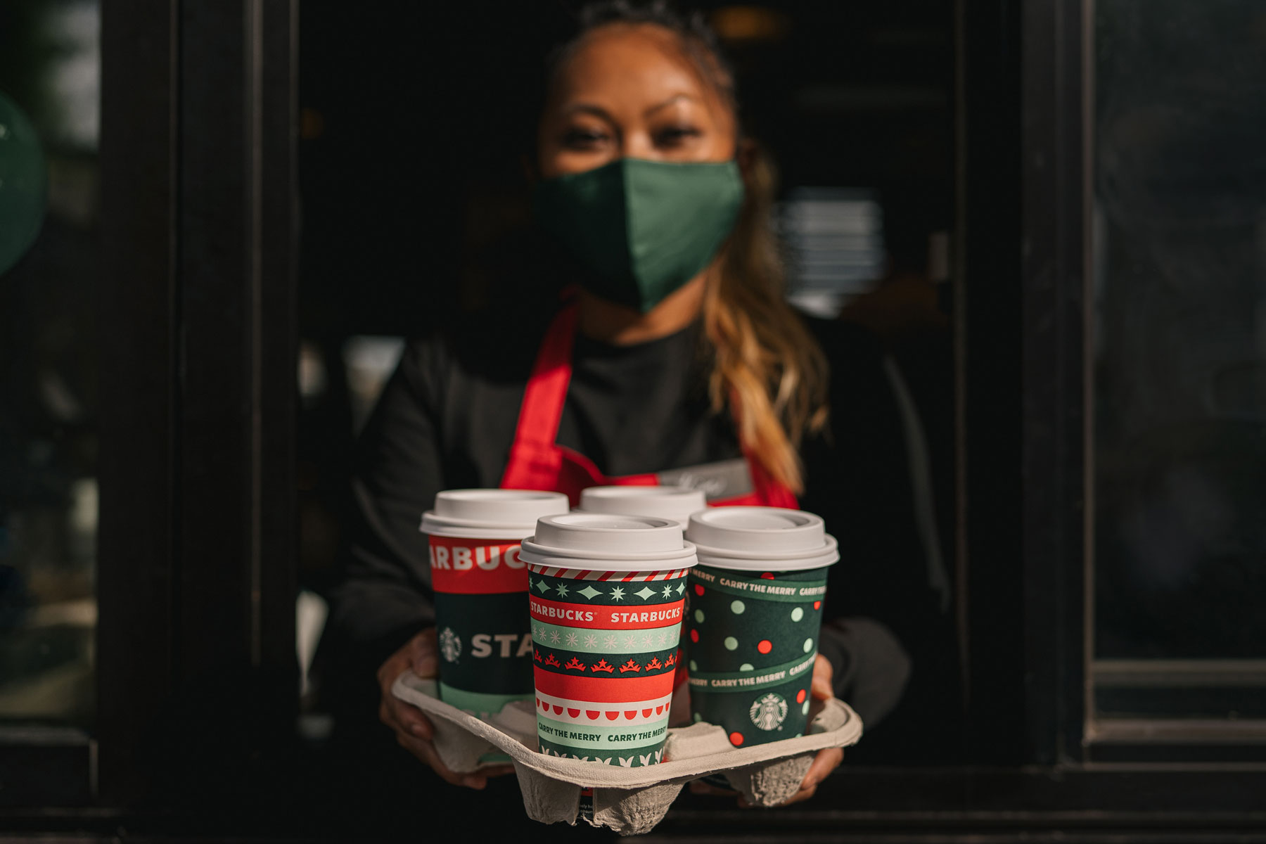 Starbucks employee holding holiday cups
