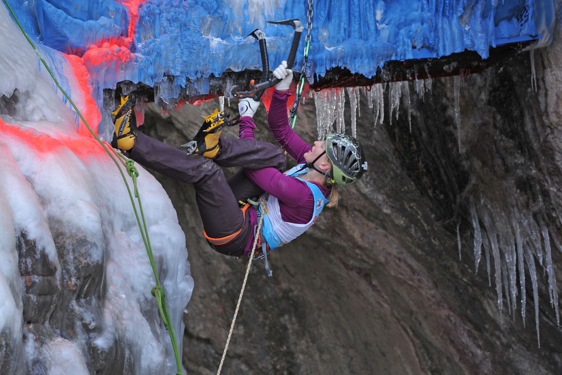 female rock climber scaling an icy rock