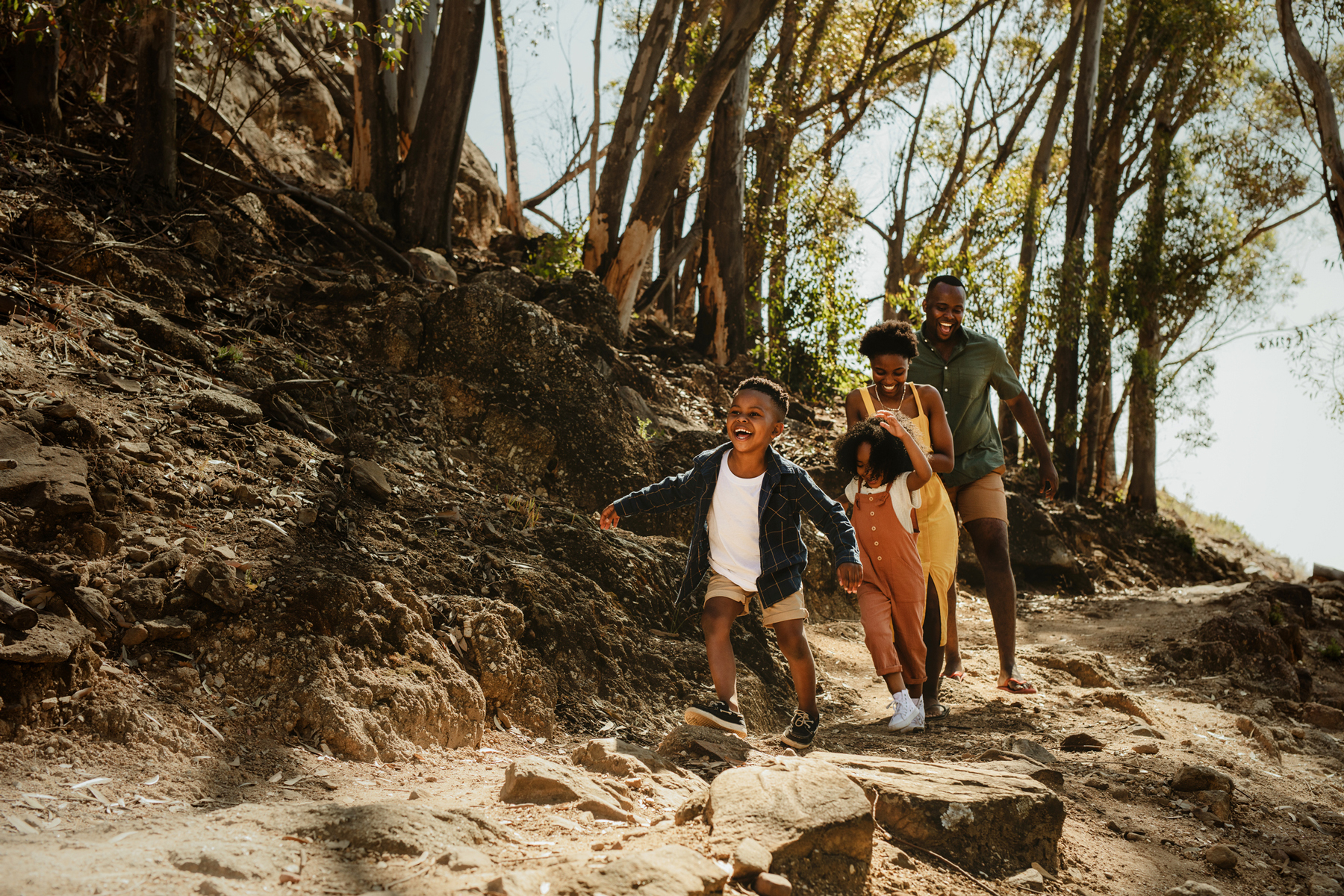Young family running down rocky mountain trail