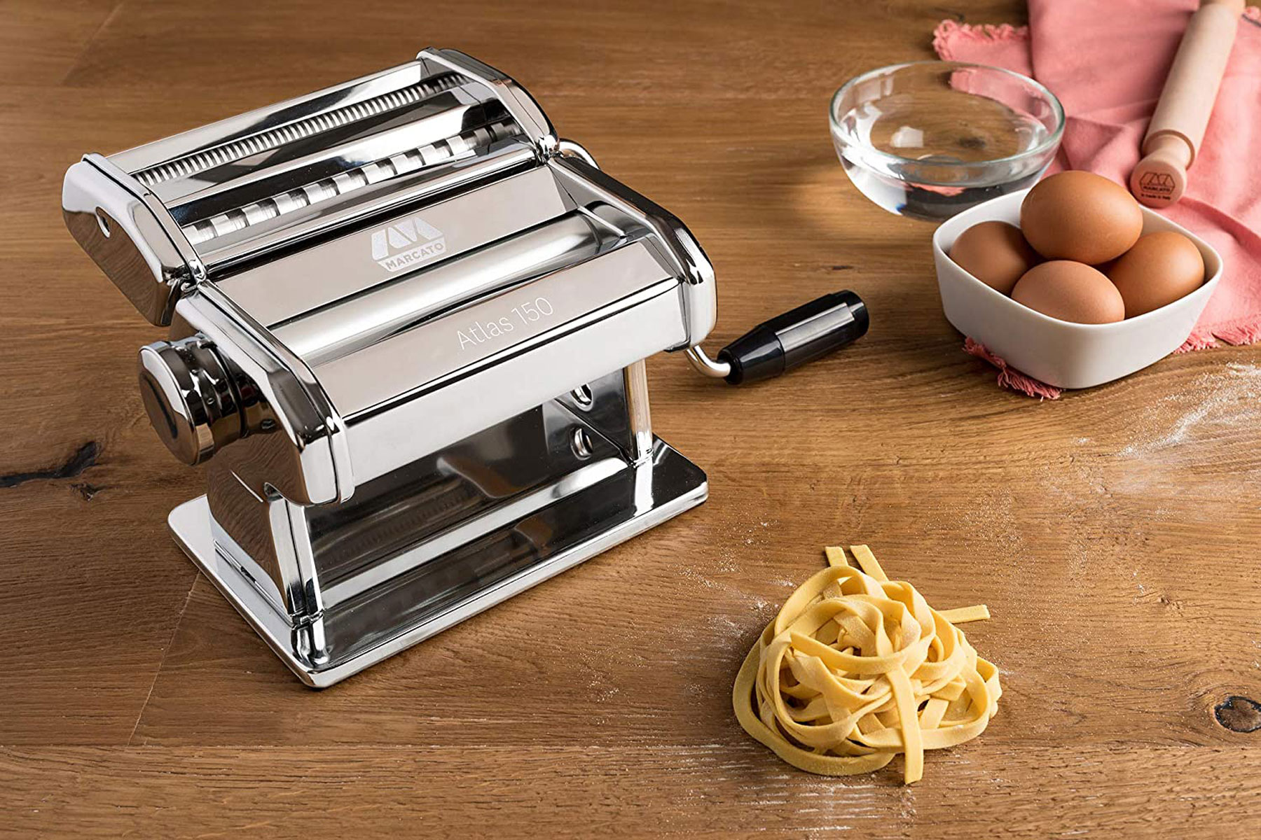 Silver pasta machine on wooden table