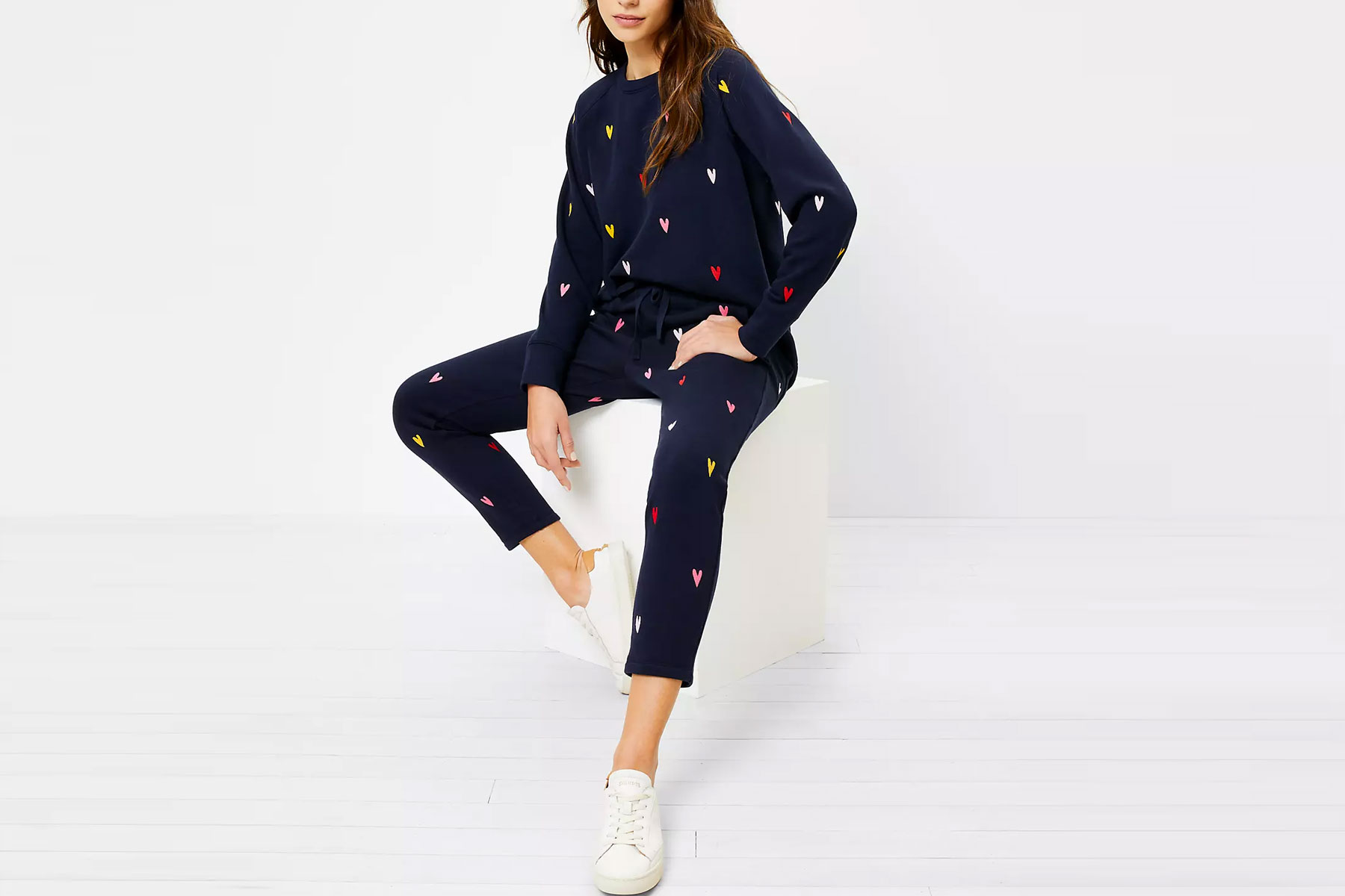 Woman wearing navy sweatsuit with multi colored hearts