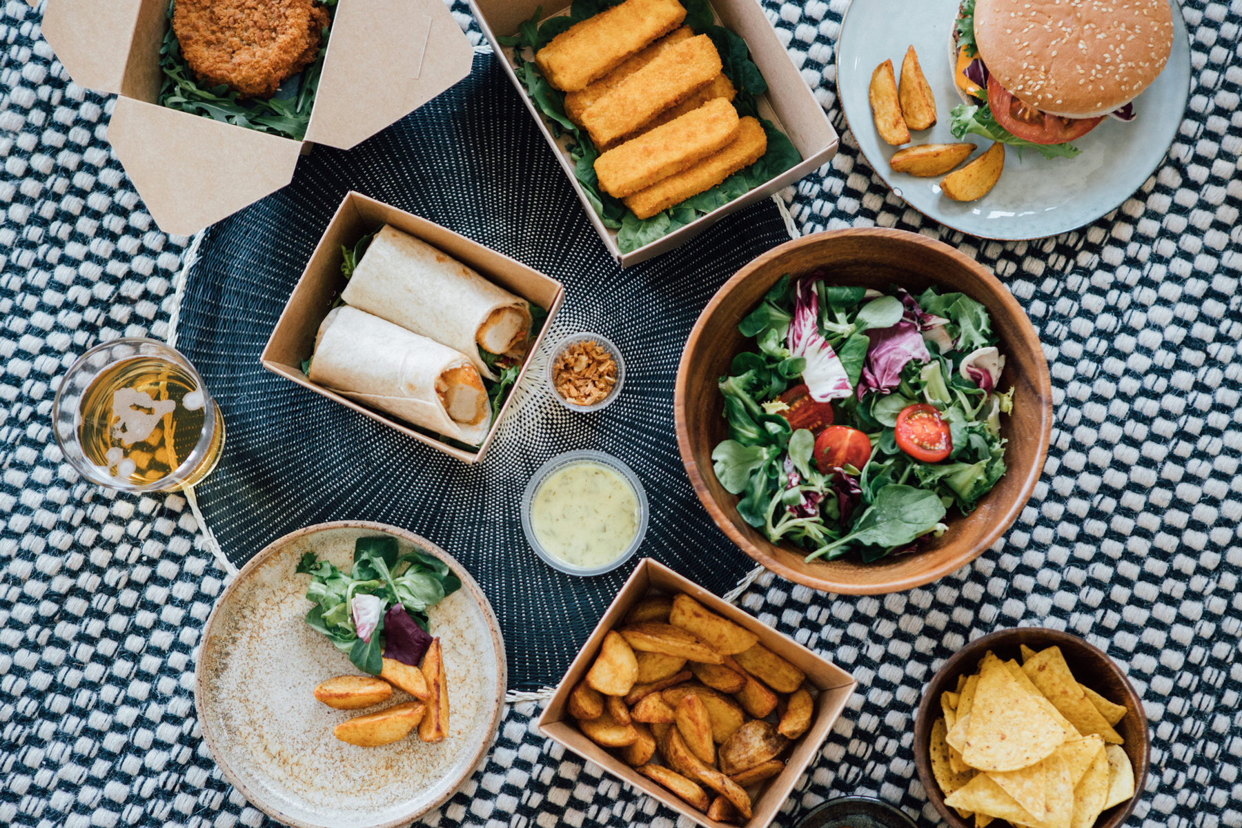 Flat lay view of delicious takeaway fast food meal - with burger, wrap sandwich, fish cake, fish sticks, potato wedges and vegetable salad.