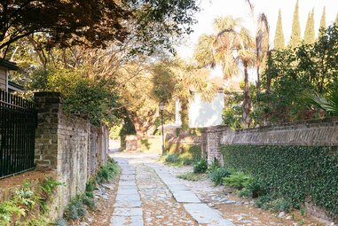 Longitude Lane off East Bay St is a traditional cobblestone pathway in the historic district of Charleston, South Carolina that was constructed near the early 18th Century. It is shady on a bright, sunny, spring day, exterior brick walls line the narrow road.