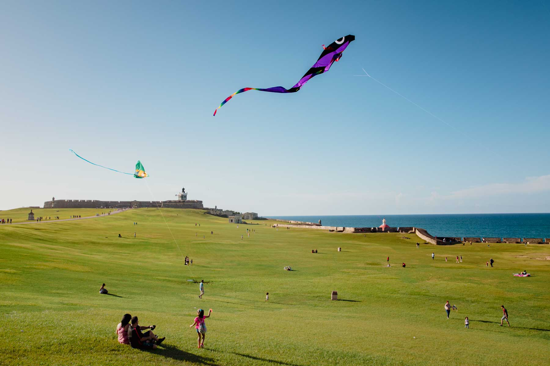 Children fly kites at El Morro, San Juan, on a sunny day