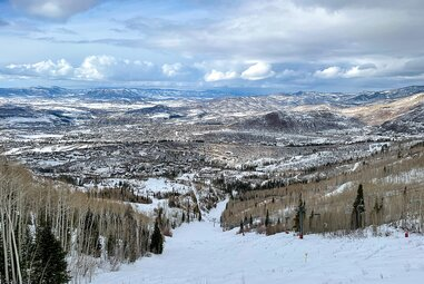 View of Rocky Mountains and a ski run on Snowmass ski resort.