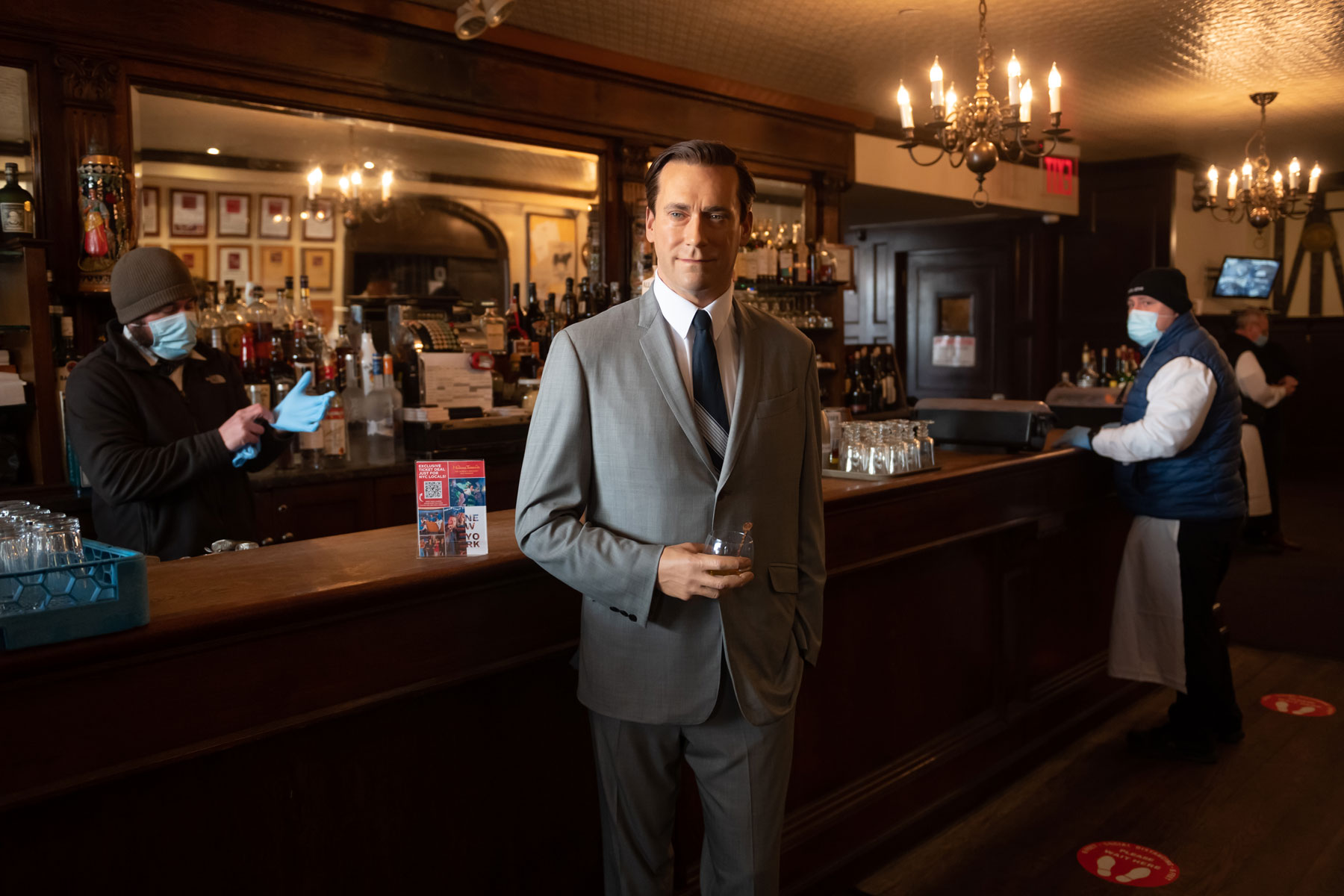 Madame Tussaud's Jon Hamm wax figure holds a glass of whiskey by the bar