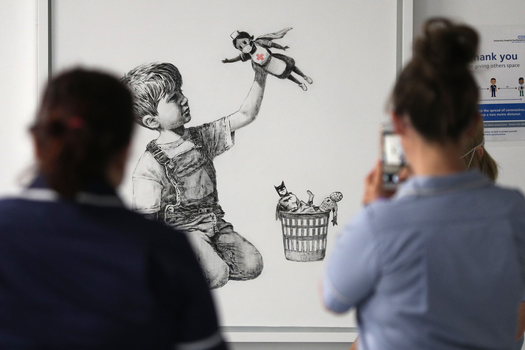 nurses view Banksy's 'Game Changer' on display at a UK hospital