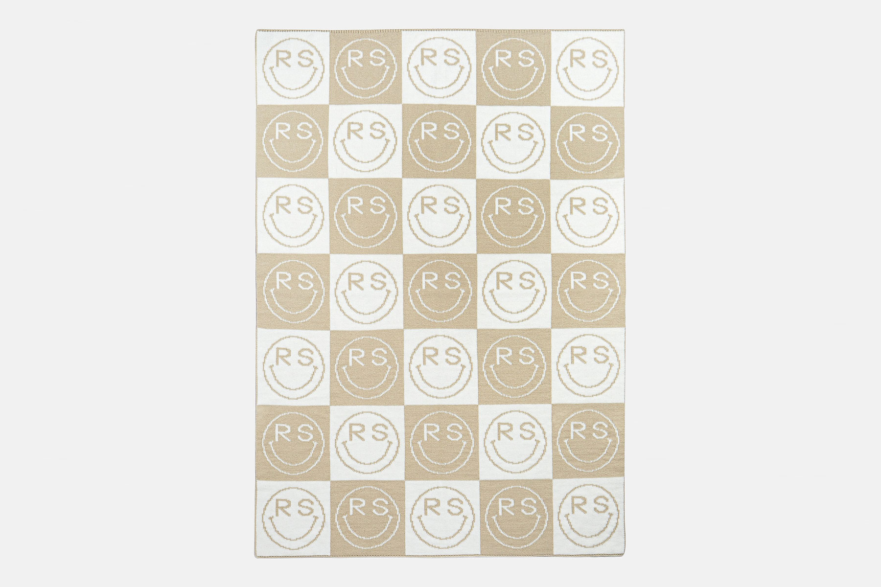 Cream and tan blanket with smiley faces