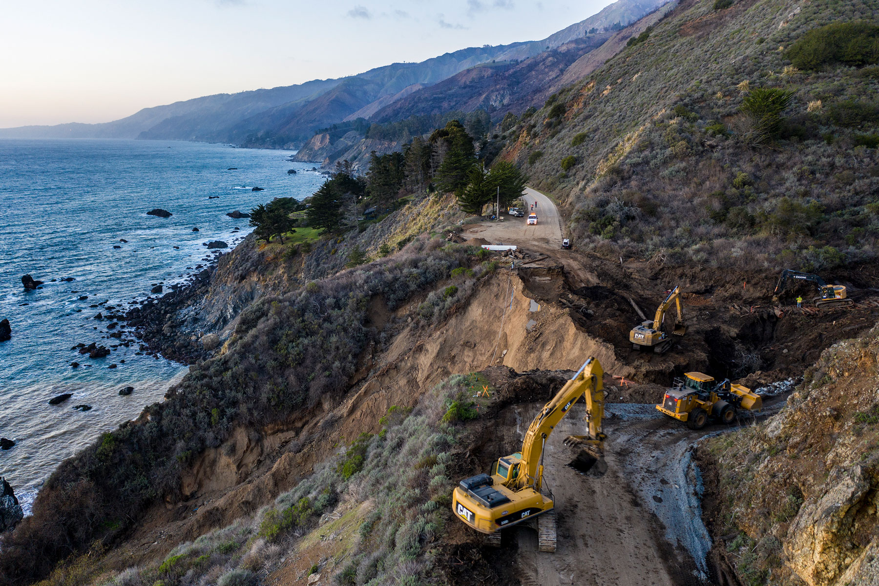 construction crews dig debris from a washed out section of Highway 1