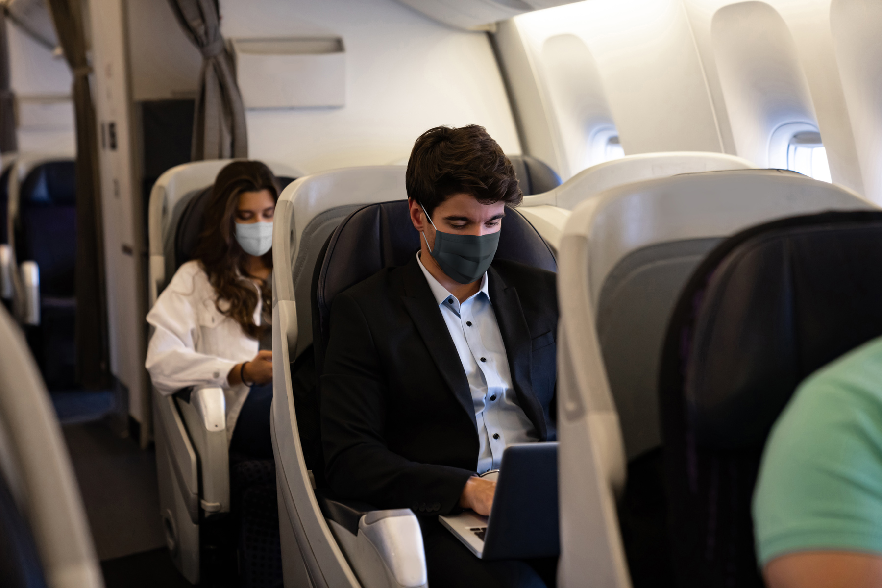 businessman wearing face mask on an airplane