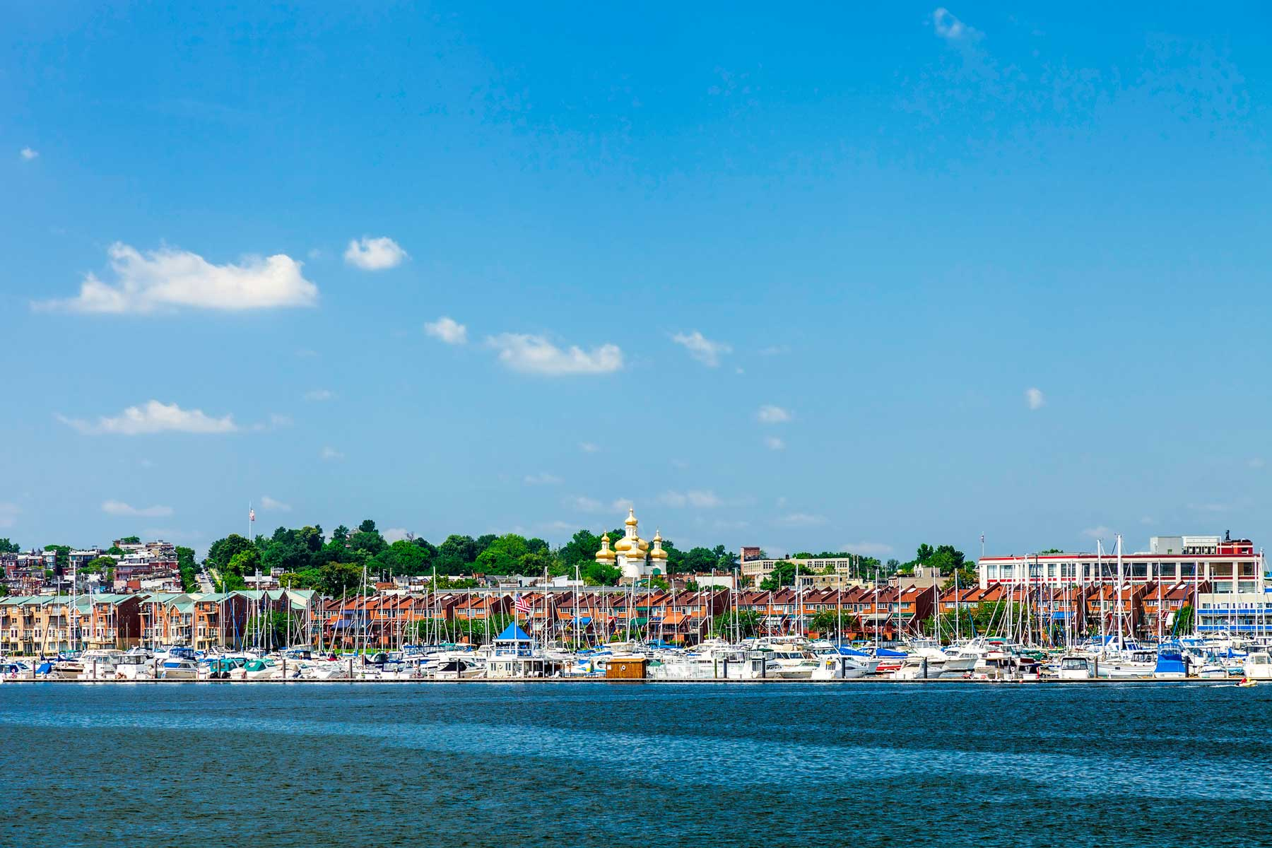 The Baltimore Inner Harbor Area where a Marina is enjoyed by many boaters and the gold topped St. Michael Ukrainian Orthodox Church on Eastern Avenue can be seen in the background.