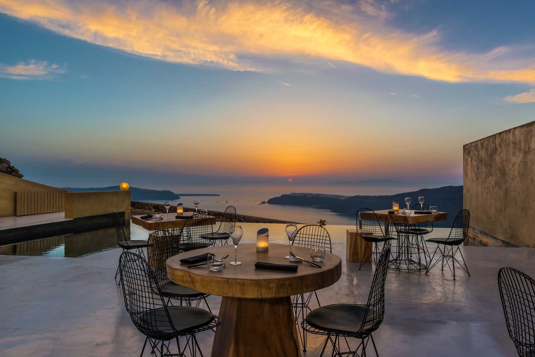 Outdoor dining at Andronis Concept Wellness Resort in Santorini with a stunning sunset view