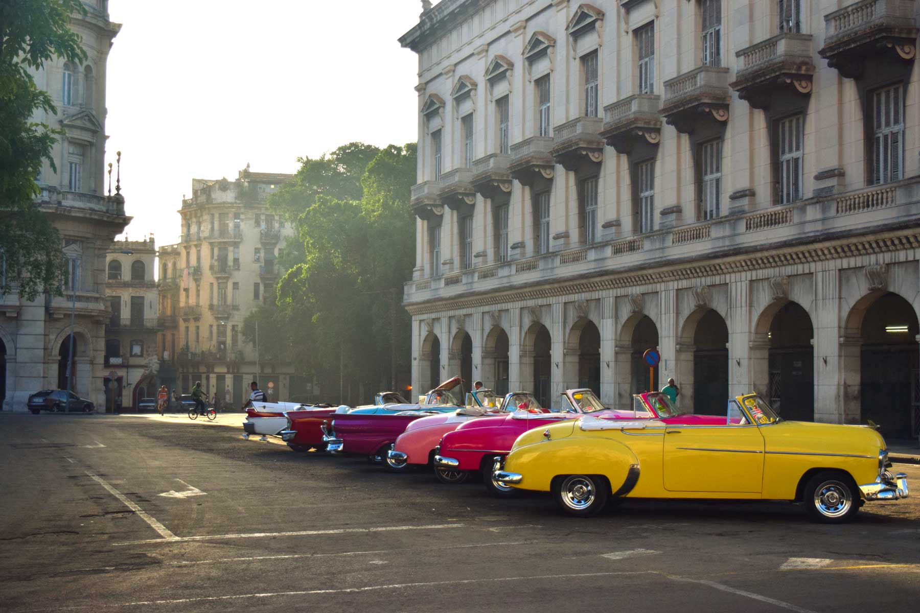 Havana, Cuba, UNESCO World Heritage Site showing vintage cars parked in the historic city center at sunrise.
