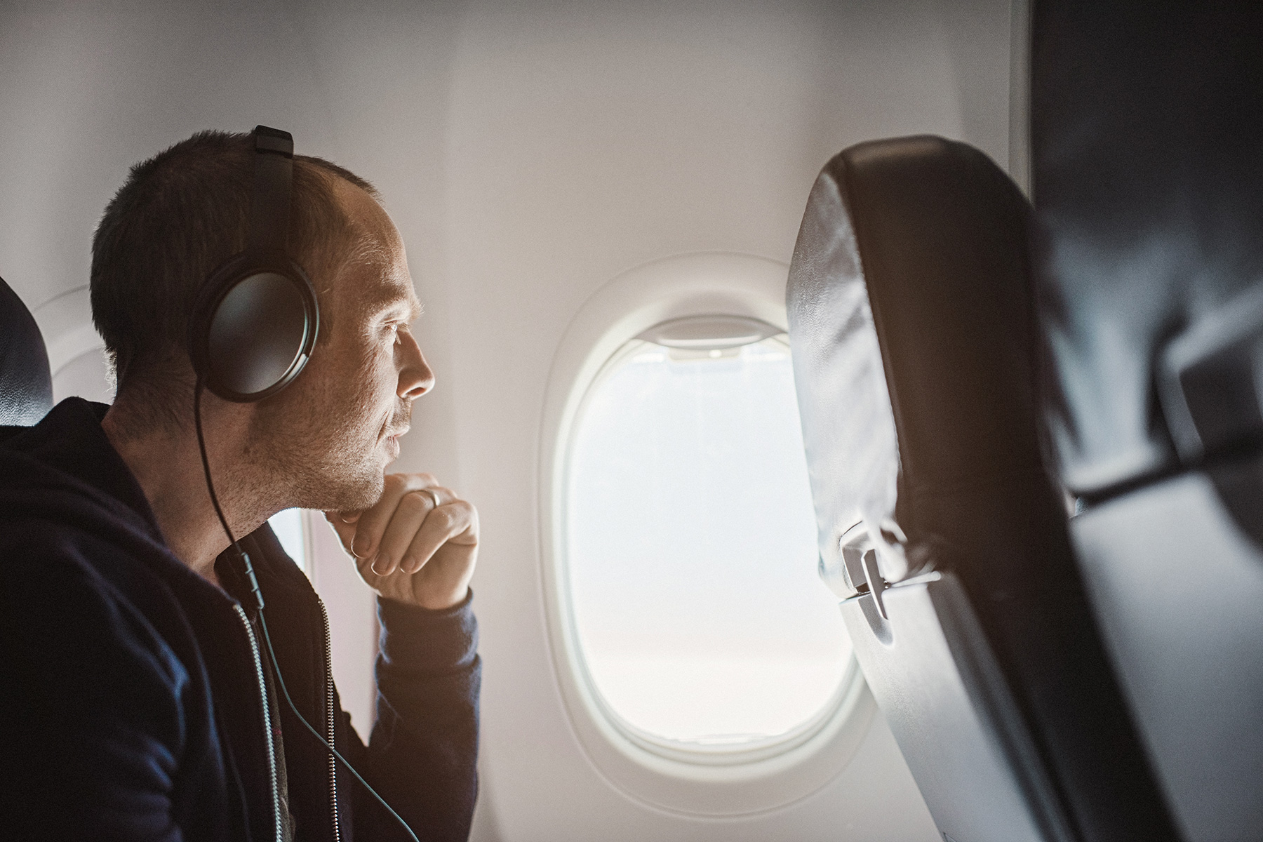 Traveling man on an airplane with noise-cancelling headphones
