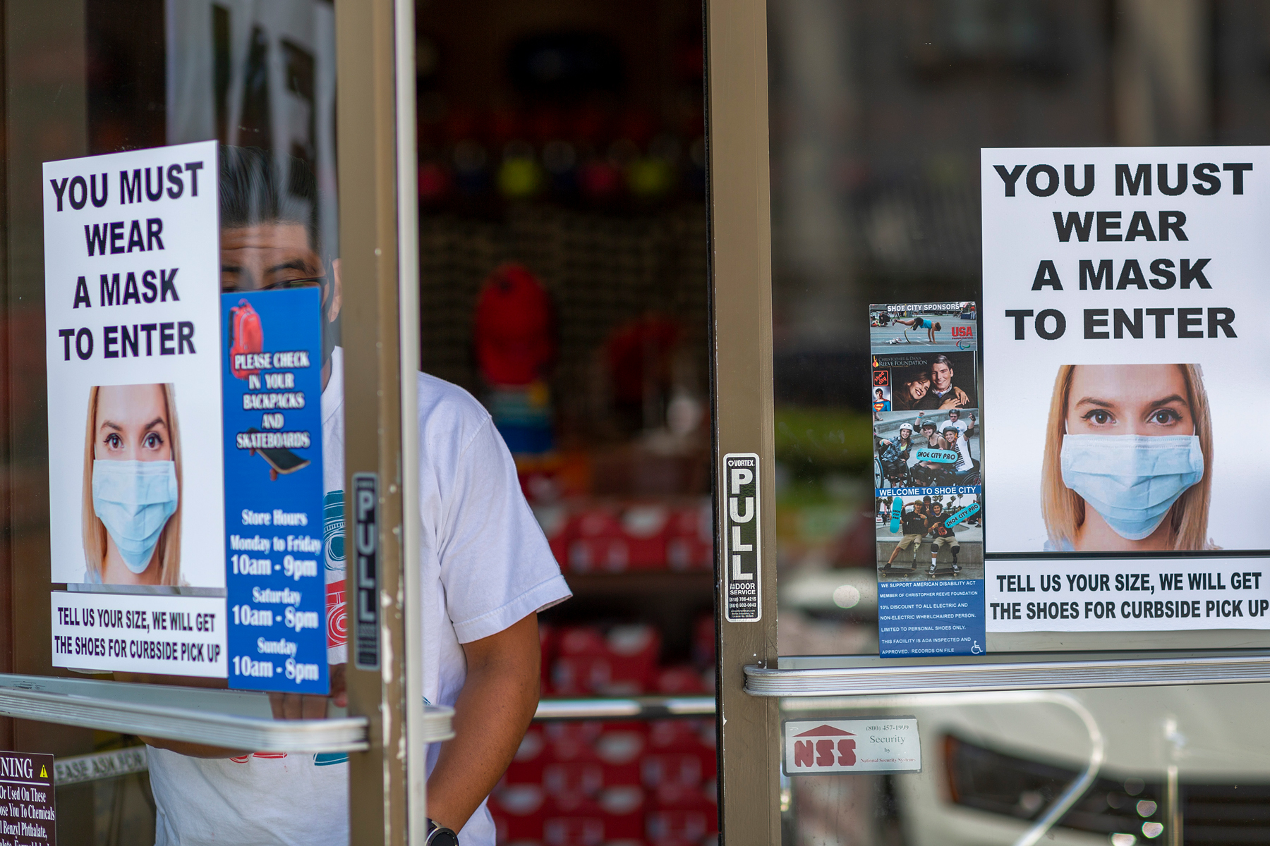 A man exits a Shoe City store where masks are required for entry as Los Angeles County retail businesses reopen while the COVID-19