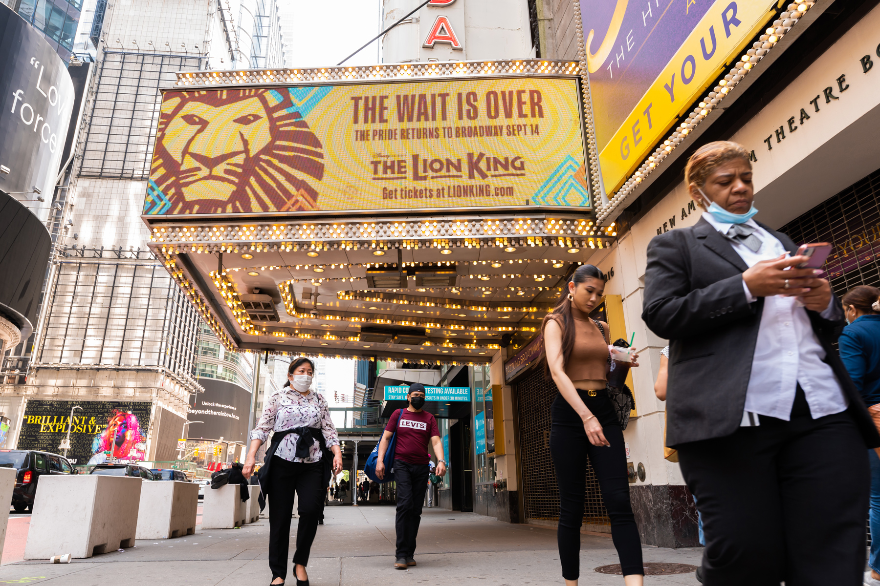 people walk by a billboard for The Lion King at the New Amsterdam Theatre in Times Square