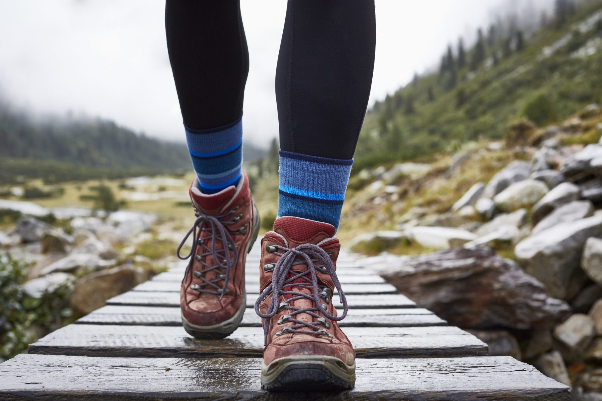 Female hiker hiking across wooden footbridge, cropped view of legs and hiking boots