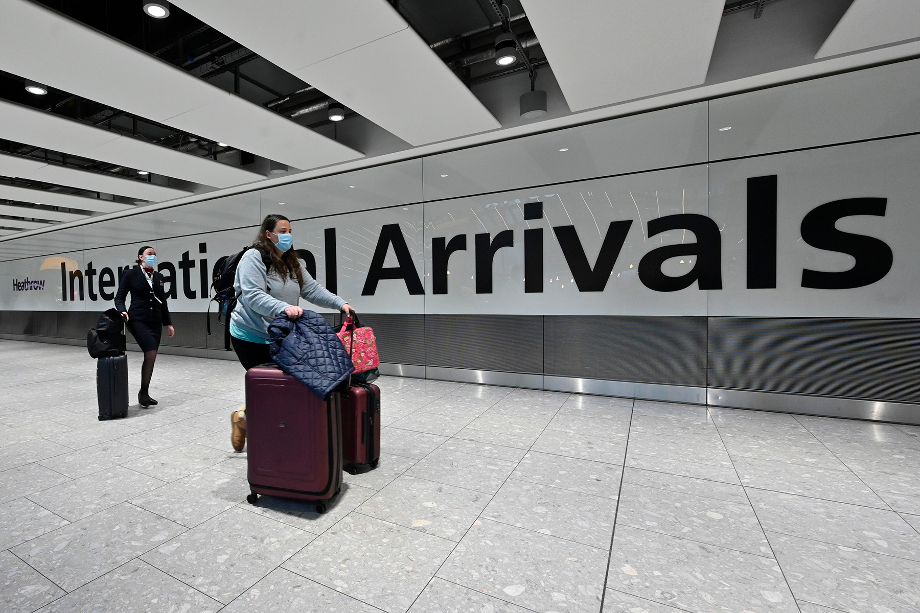 Passengers arrive with lugagge at the Terminal 5 international arrivals hall at London Heathrow Airport