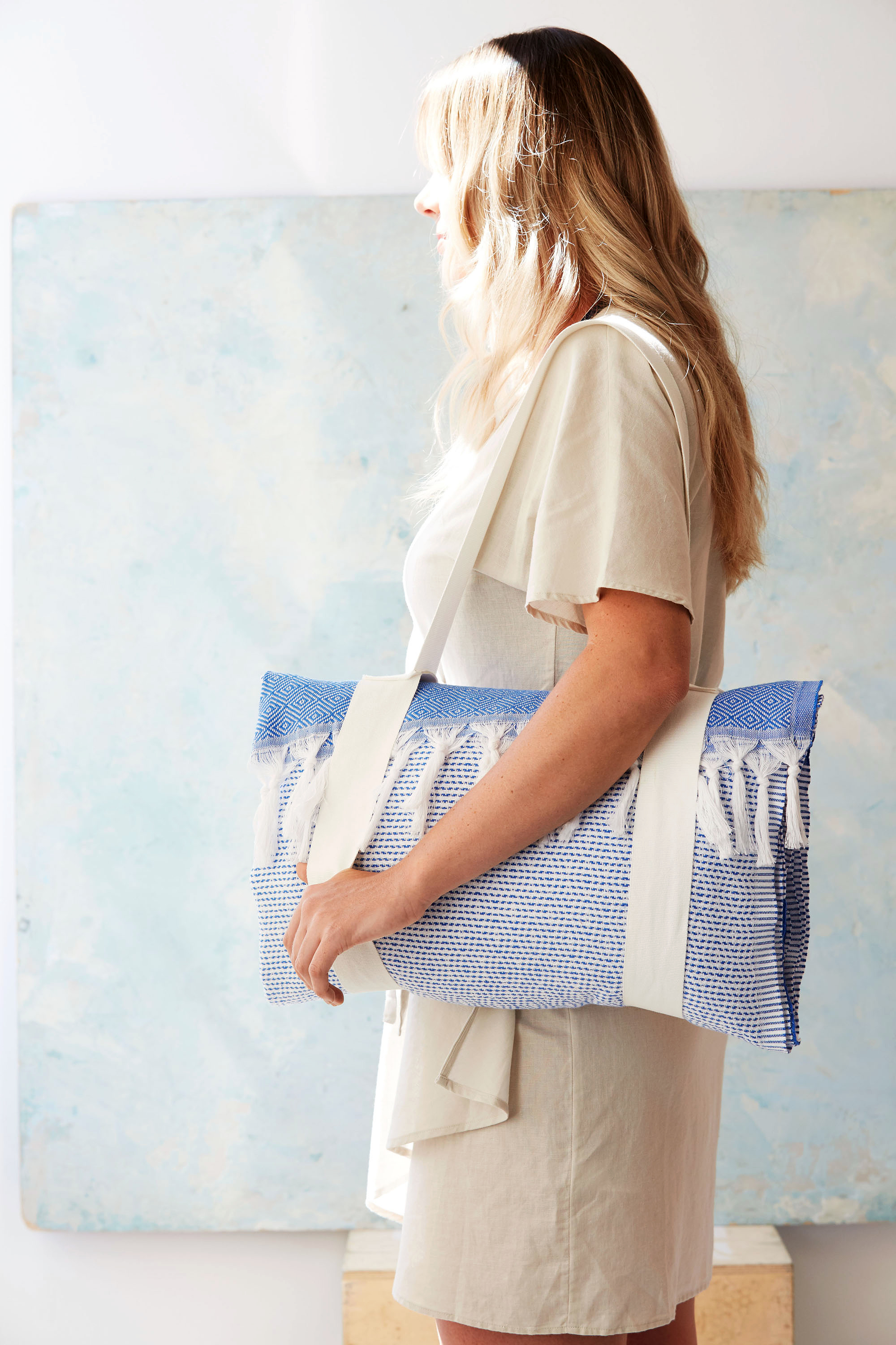 woman holding beach towel tote bag