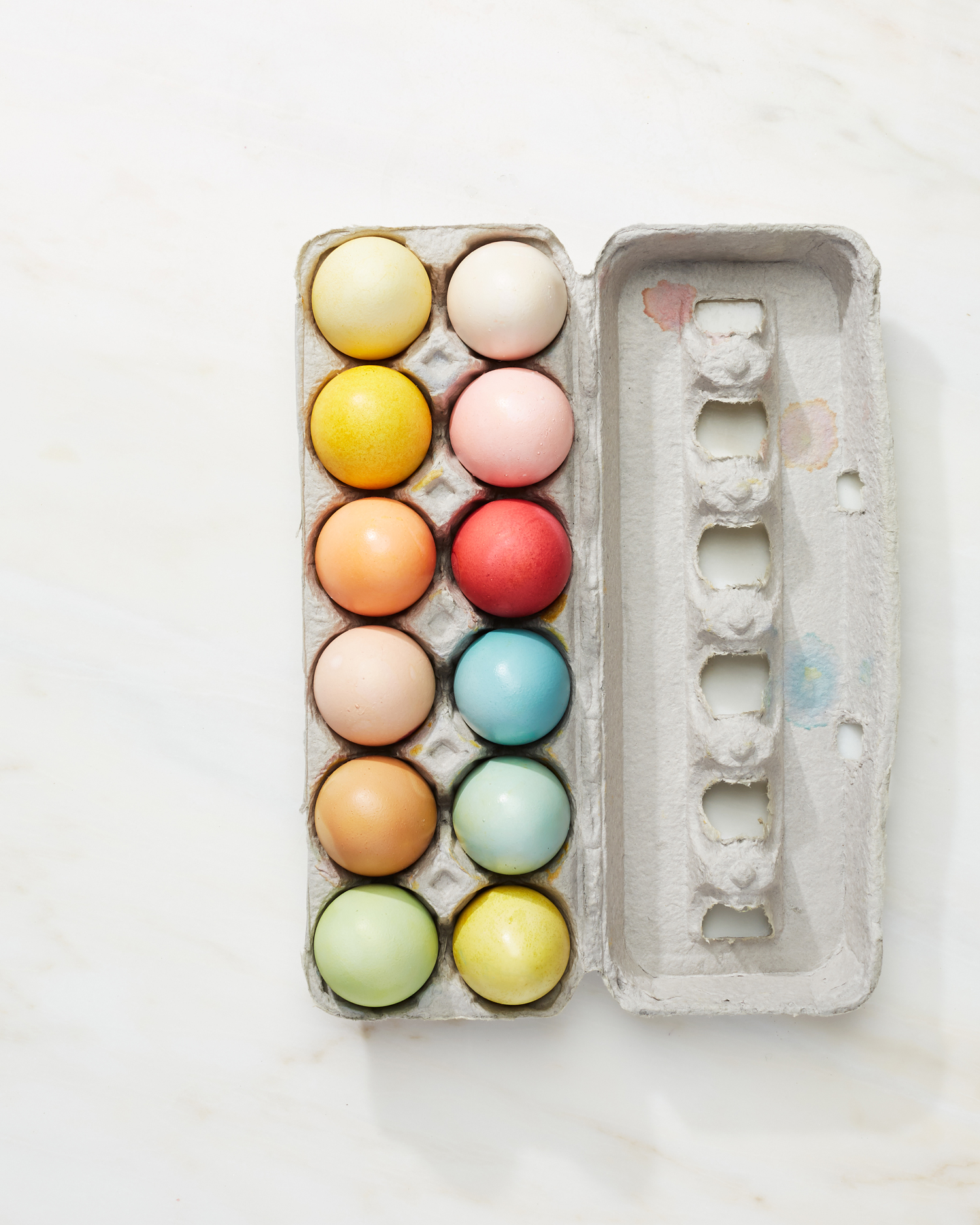 naturally dyed easter eggs in an egg carton